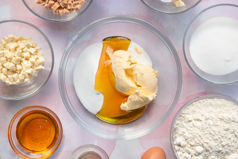 Overhead shot of margarine, golden syrup and sugar in a large clear bowl