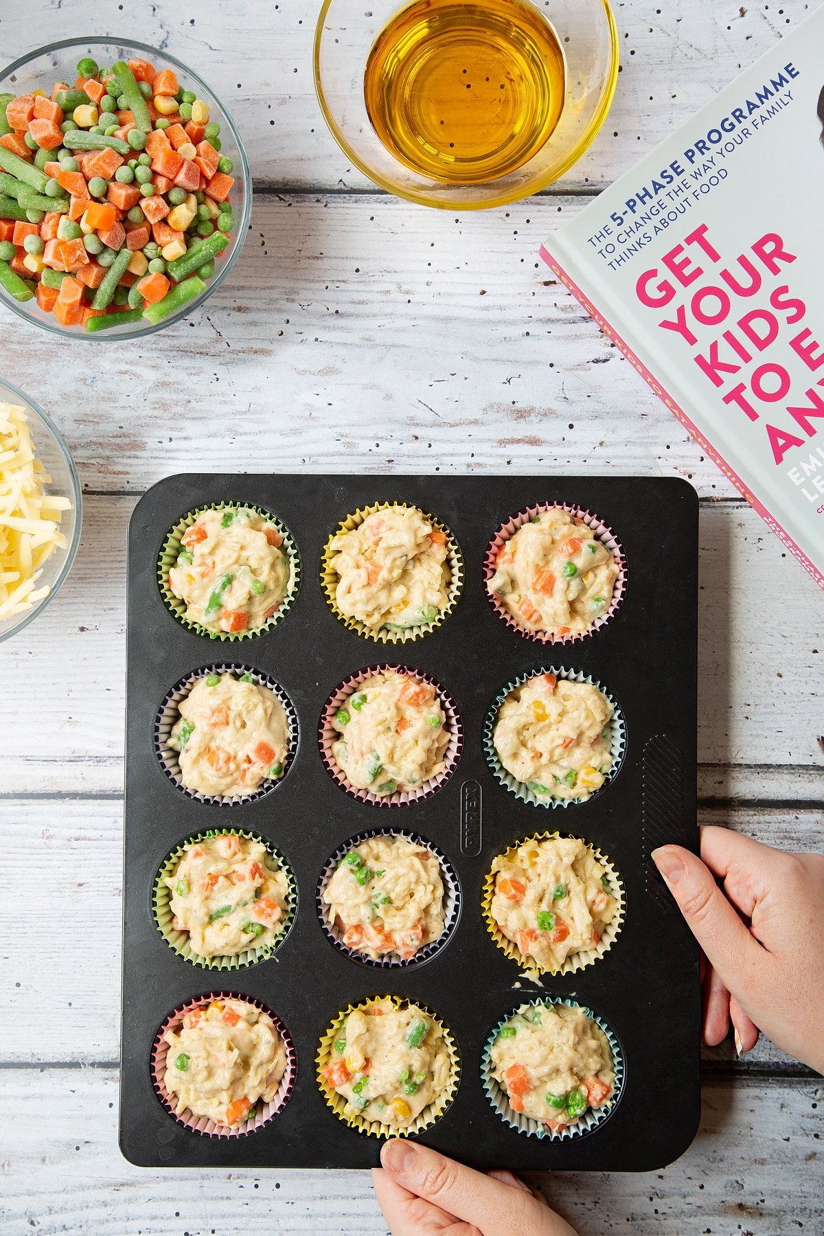 A 12-hole muffin tray lined with muffins cases and filled with savoury muffin batter with cheese and mixed chopped vegetables. The tray is surrounded by the ingredients for savoury vegetable muffins.