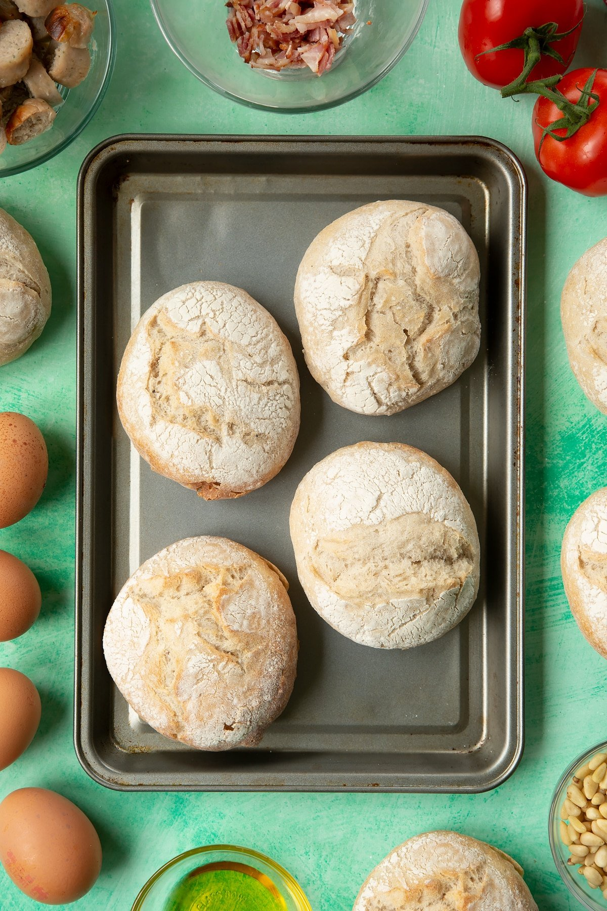Four crusty bread rolls on a baking tray. The tray is surrounded by ingredients to make breakfast rolls.