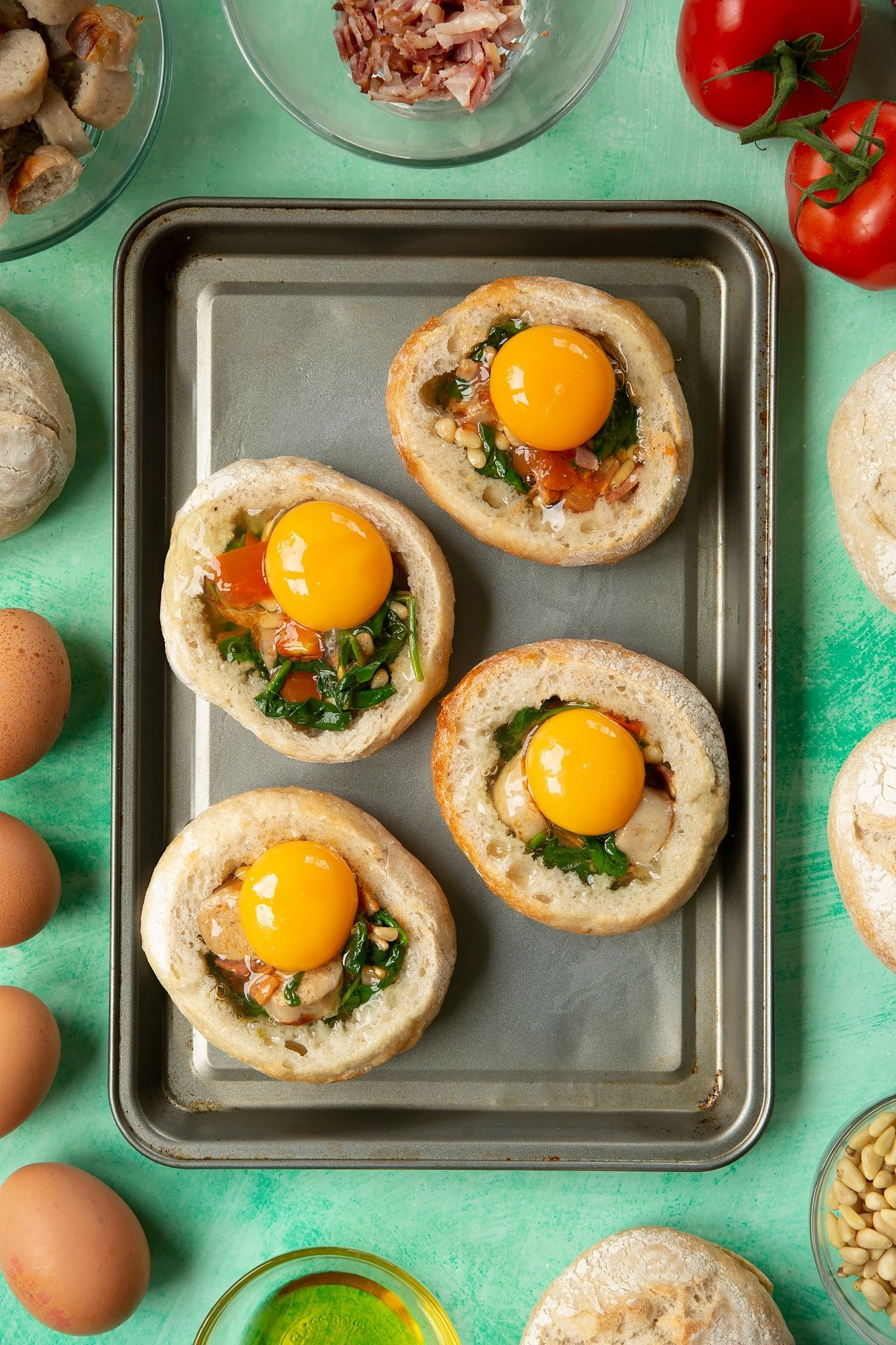 Four bread rolls on a baking tray. The rolls are hollowed out and filled with a mix of fried sausage, bacon, chopped tomatoes, pine nuts and wilted spinach, and topped with eggs. The tray is surrounded by ingredients to make breakfast rolls.