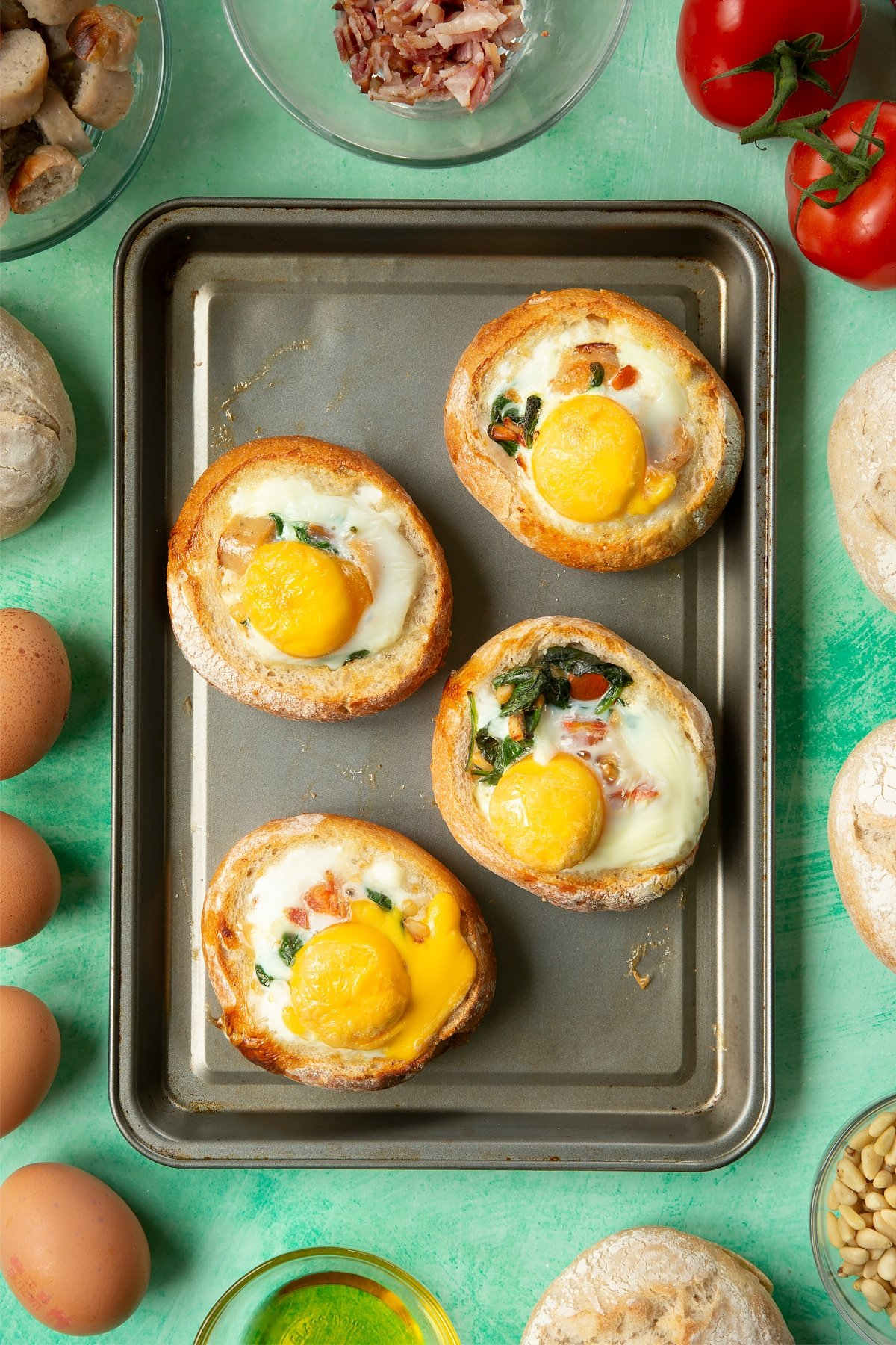 Four bread rolls on a baking tray. The rolls are hollowed out and filled with a mix of fried sausage, bacon, chopped tomatoes, pine nuts and wilted spinach, and topped with baked eggs. The tray is surrounded by ingredients to make breakfast rolls.