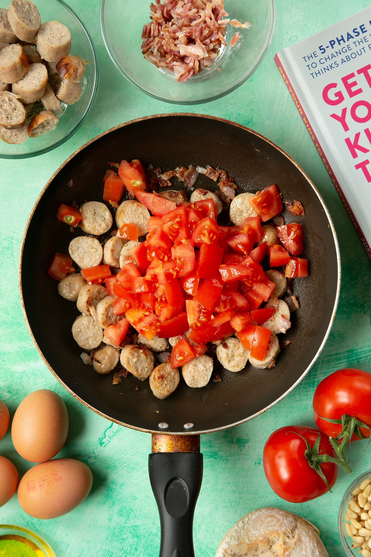 A frying pan containing fried sausage and bacon, topped with chopped tomatoes. The pan is surrounded by ingredients to make breakfast rolls.