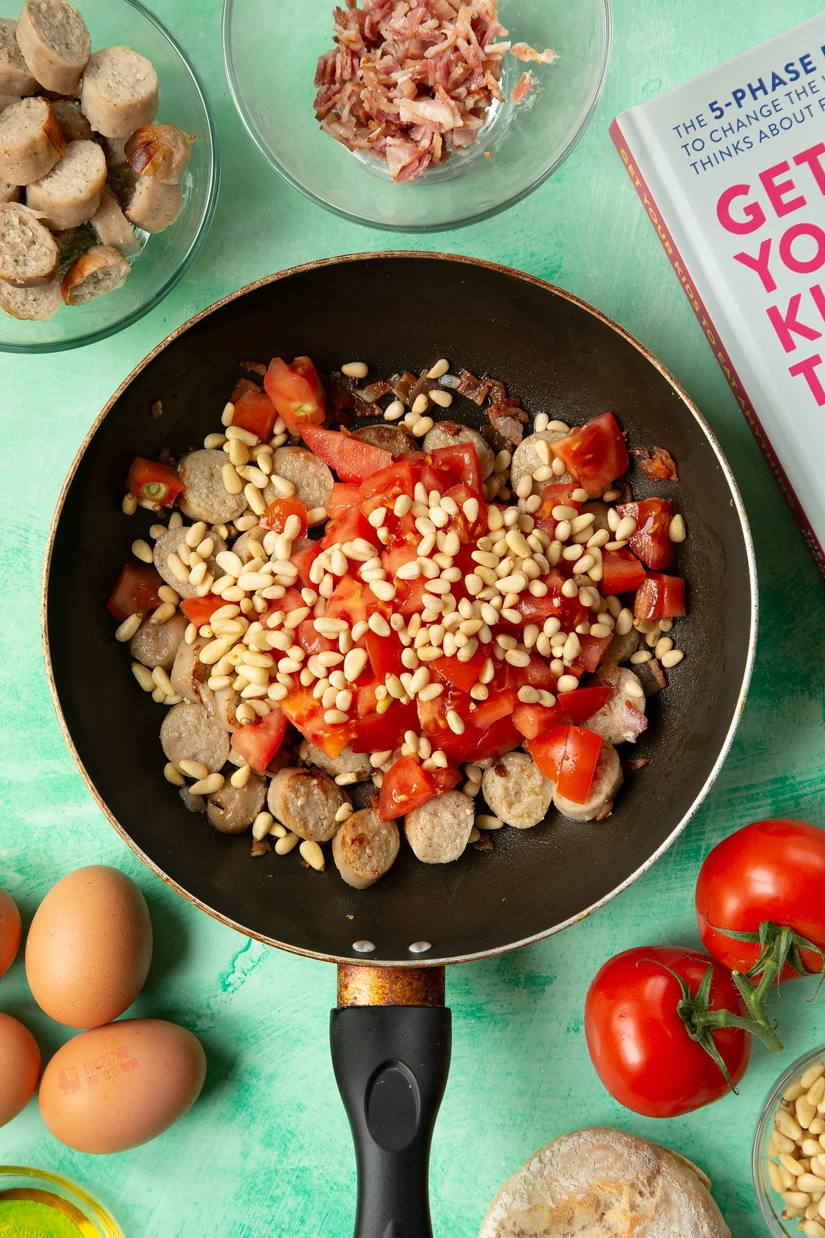 A frying pan containing fried sausage and bacon, topped with chopped tomatoes and pine nuts. The pan is surrounded by ingredients to make breakfast rolls.