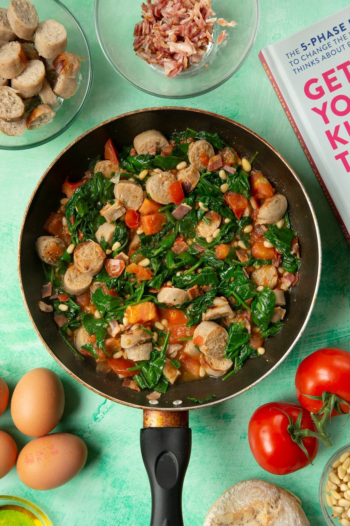 A frying pan containing fried sausage, bacon, chopped tomatoes, pine nuts and wilted spinach. The pan is surrounded by ingredients to make breakfast rolls.