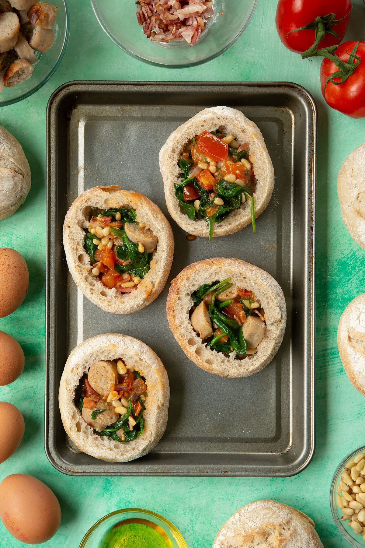Four bread rolls on a baking tray. The rolls are hollowed out and filled with a mix of fried sausage, bacon, chopped tomatoes, pine nuts and wilted spinach. The tray is surrounded by ingredients to make breakfast rolls.