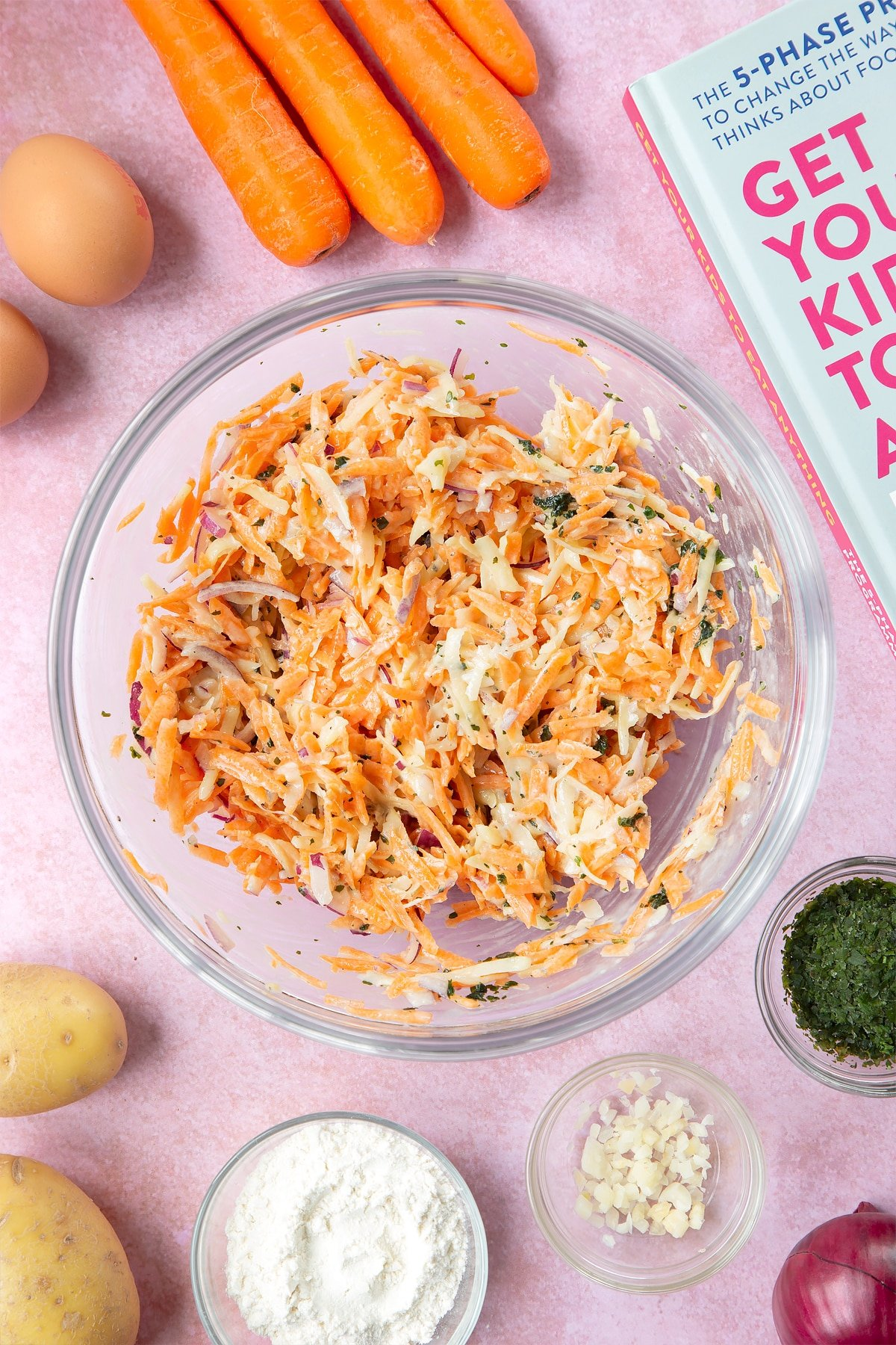 Grated carrot, potato, red onion and coriander in a flour and egg batter in a mixing bowl. The bowl is surrounded by ingredients to make carrot patties.