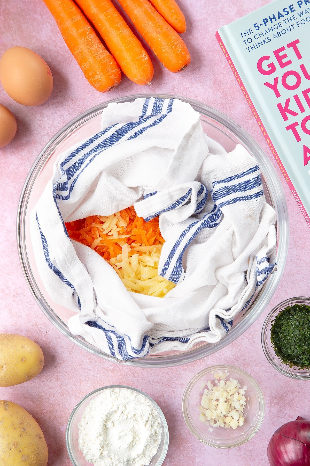 Grated carrot, red onion and potato in side a white and blue tea towel in a mixing bowl. The bowl is surrounded by ingredients to make carrot patties.