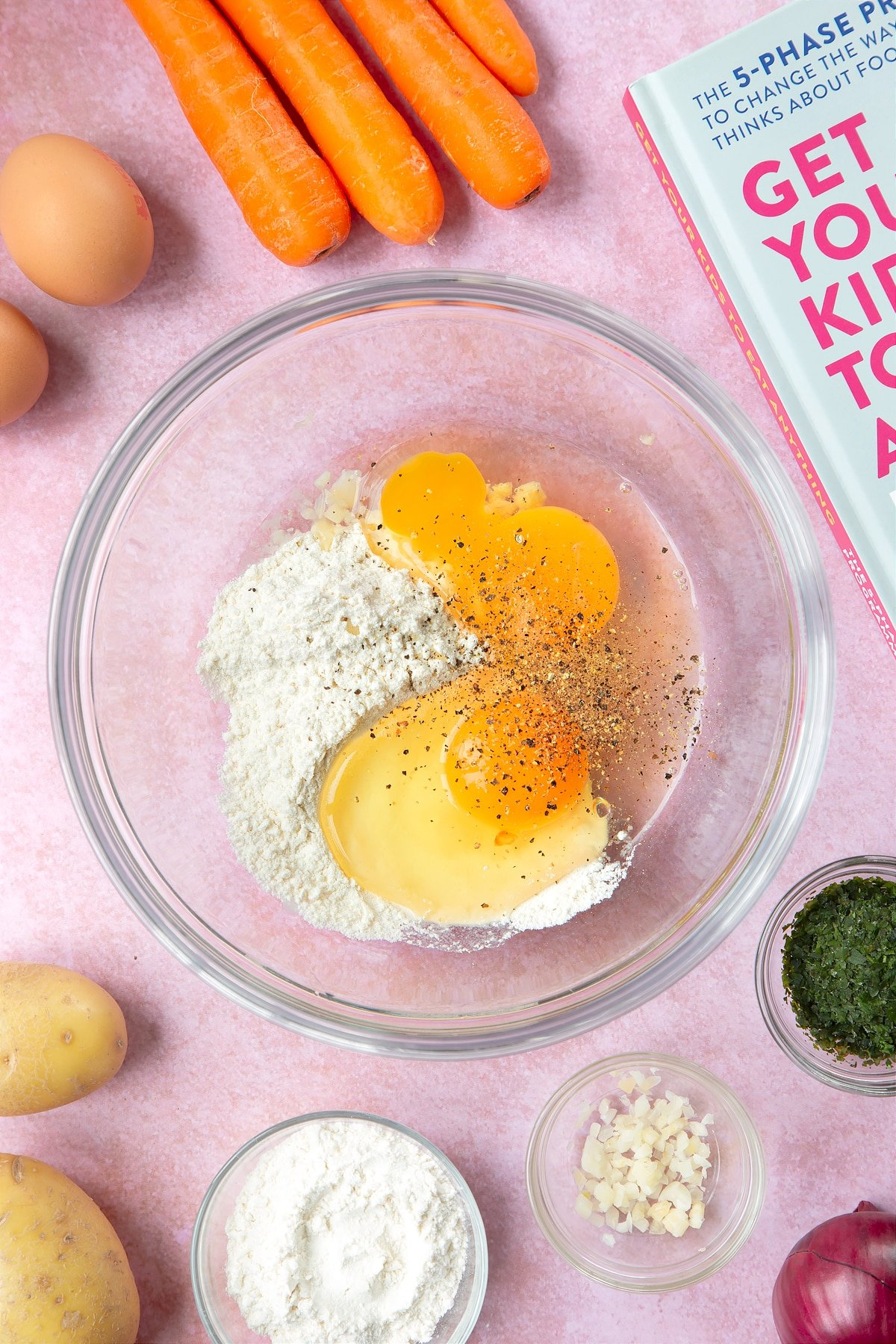 Flour, eggs, salt and pepper in a mixing bowl. The bowl is surrounded by ingredients to make carrot patties.