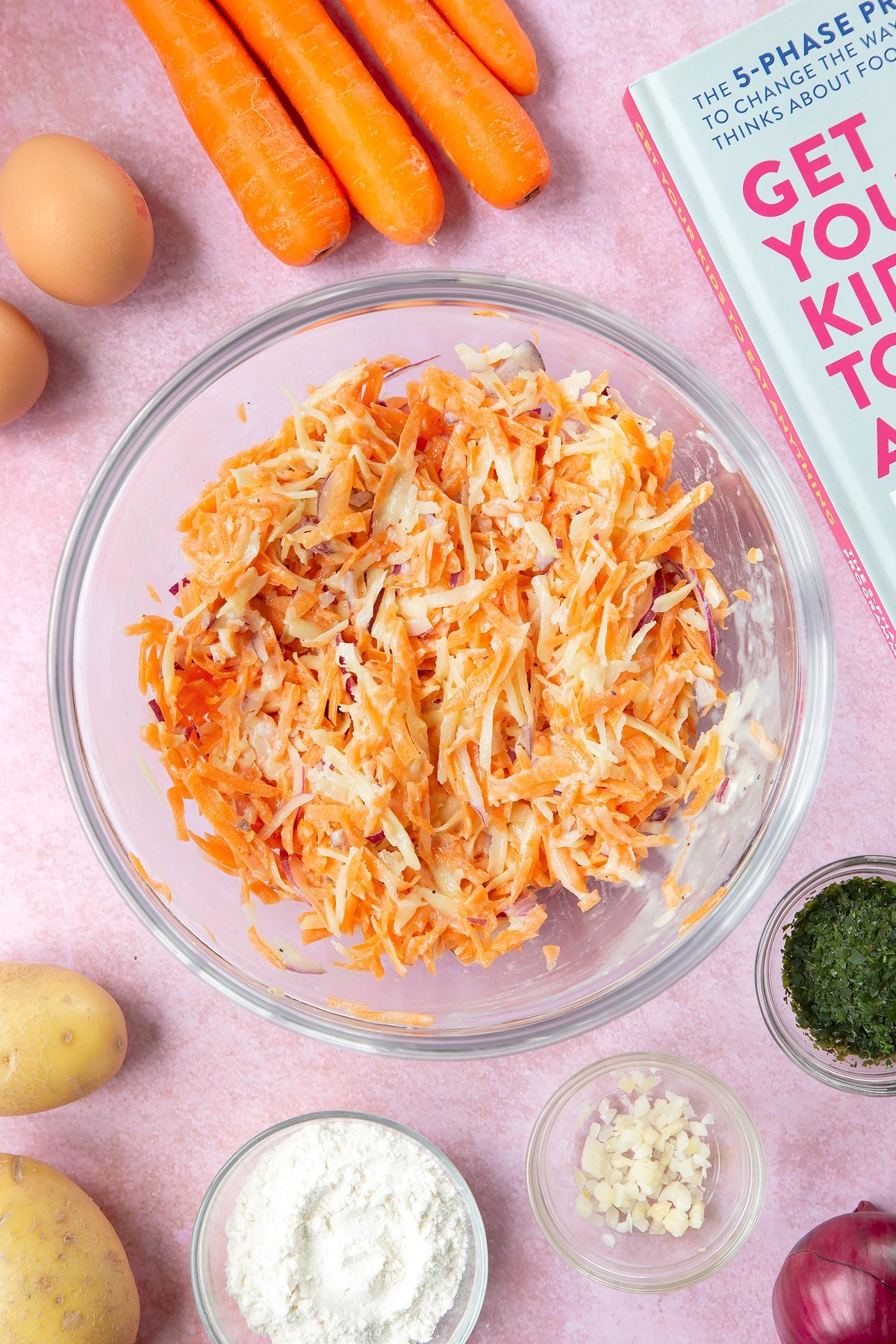 Grated carrot, potato and red onion mixed with a batter made from flour, eggs, salt and pepper in a mixing bowl. The bowl is surrounded by ingredients to make carrot patties.