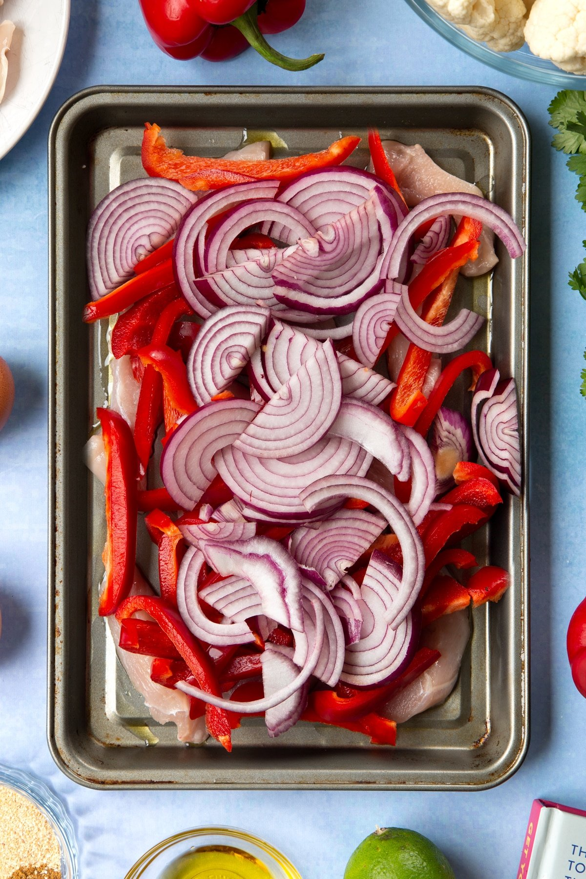 Sliced chicken breast, sliced red peppers and sliced red onion on an oiled tray. The tray is surrounded by ingredients for cauliflower tacos.