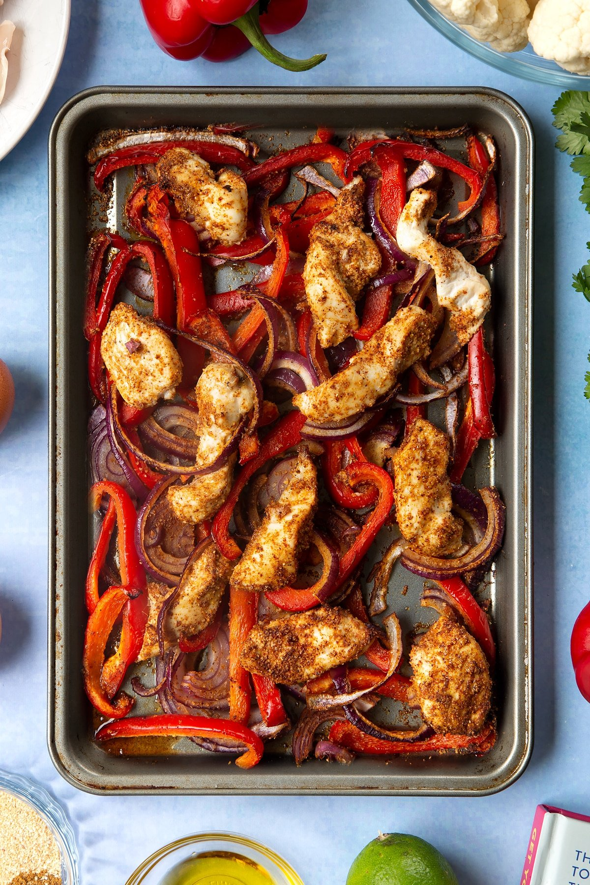 Sliced chicken breast, sliced red peppers, sliced red onion and spices mixed together on an oiled tray and roasted. The tray is surrounded by ingredients for cauliflower tacos.