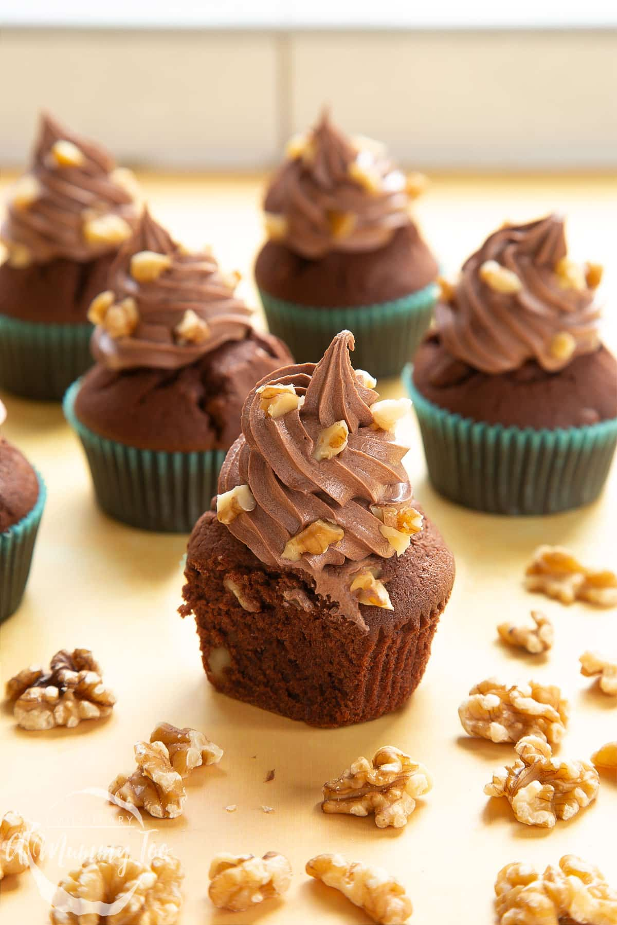 Chocolate walnut cupcakes decorated with creamy chocolate frosting. The cupcake at the fore has been cut open to show the inside.