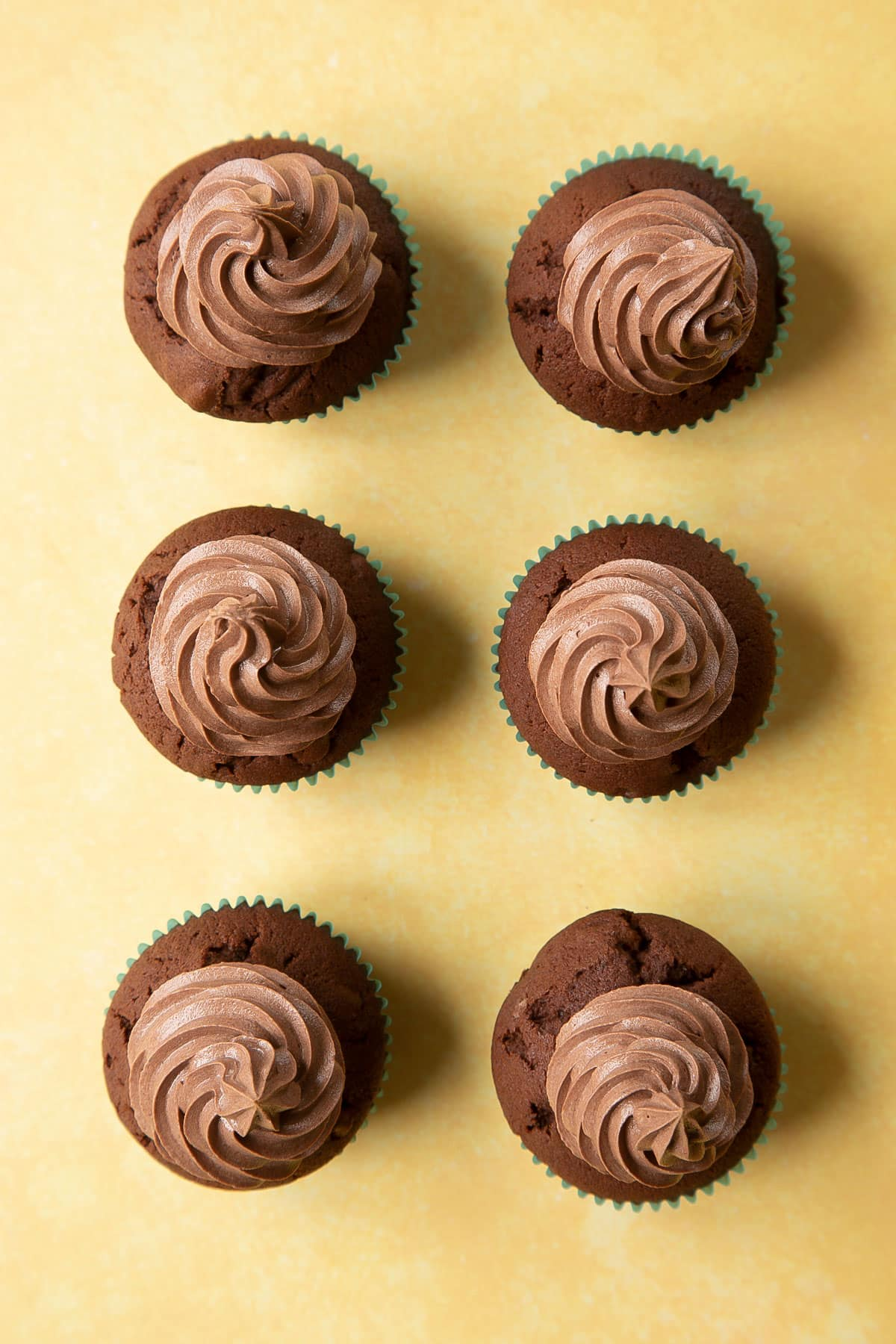 Chocolate walnut cupcakes with chocolate frosting piped on top in tall swirls.