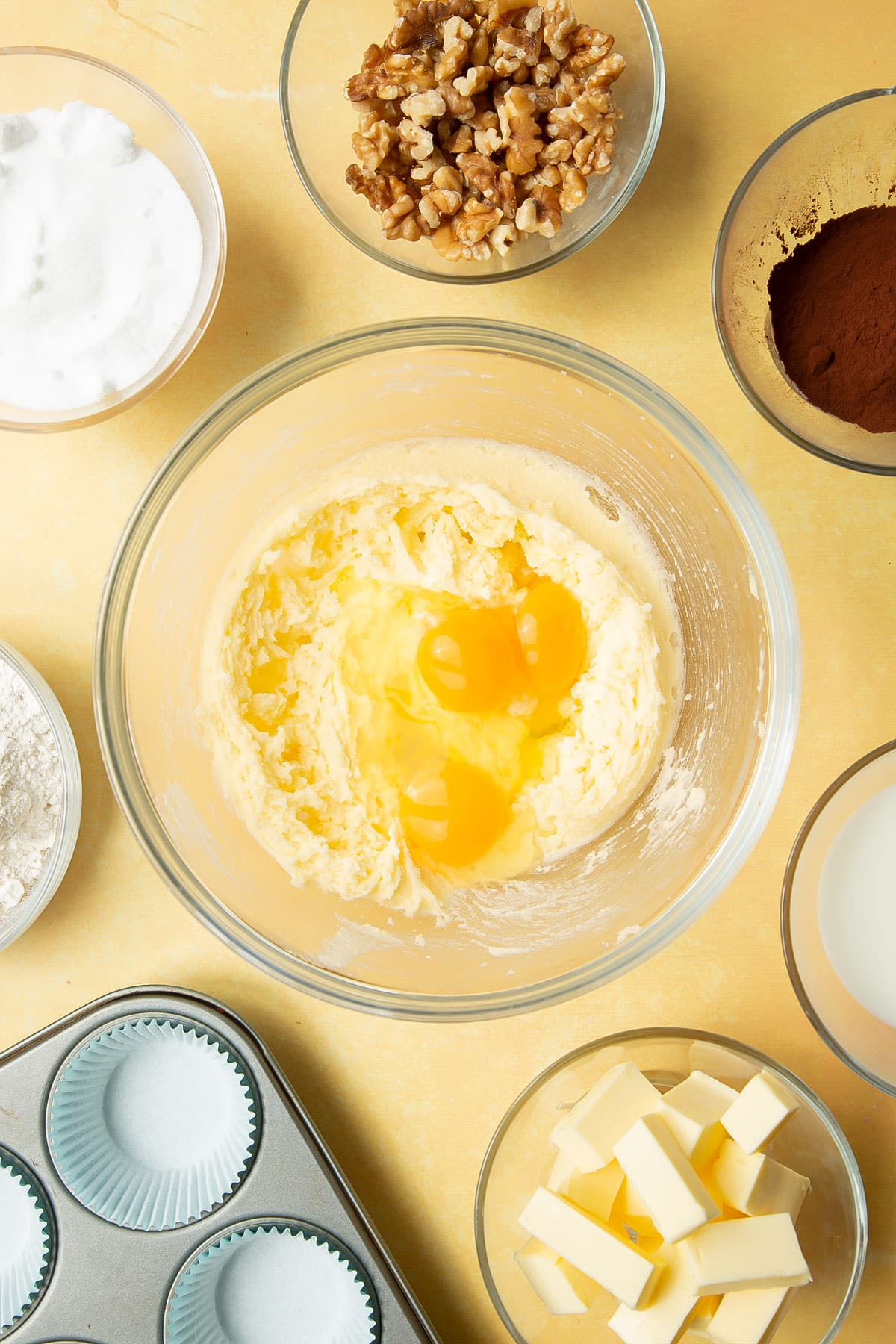 Butter and sugar, creamed together in a glass mixing bowl and topped with eggs. Ingredients for chocolate walnut cupcakes surround the bowl.