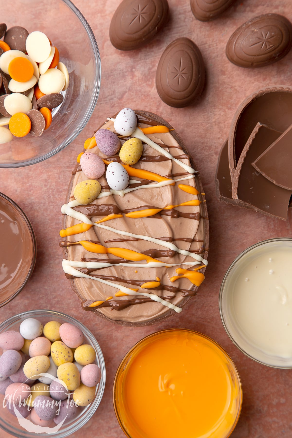 An Easter egg cheesecake on a small marble board. The chocolate cheesecake filling sits in a chocolate Easter egg shell, drizzled with white, milk and orange chocolate. The egg is surrounded by ingredients.