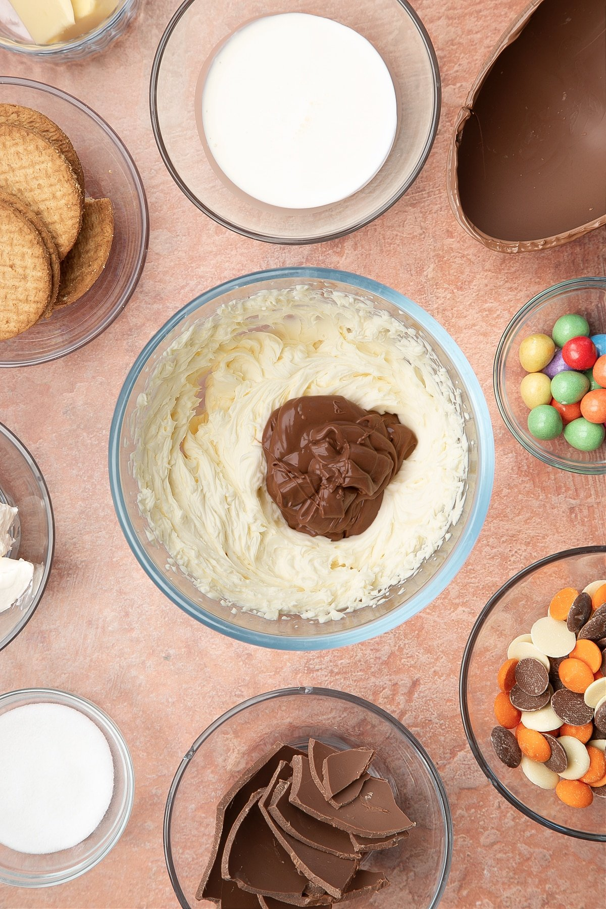 A glass bowl containing cream cheese, double cream and sugar whisked together with melted chocolate. The bowl is surrounded by ingredients to make Easter Egg cheesecake.