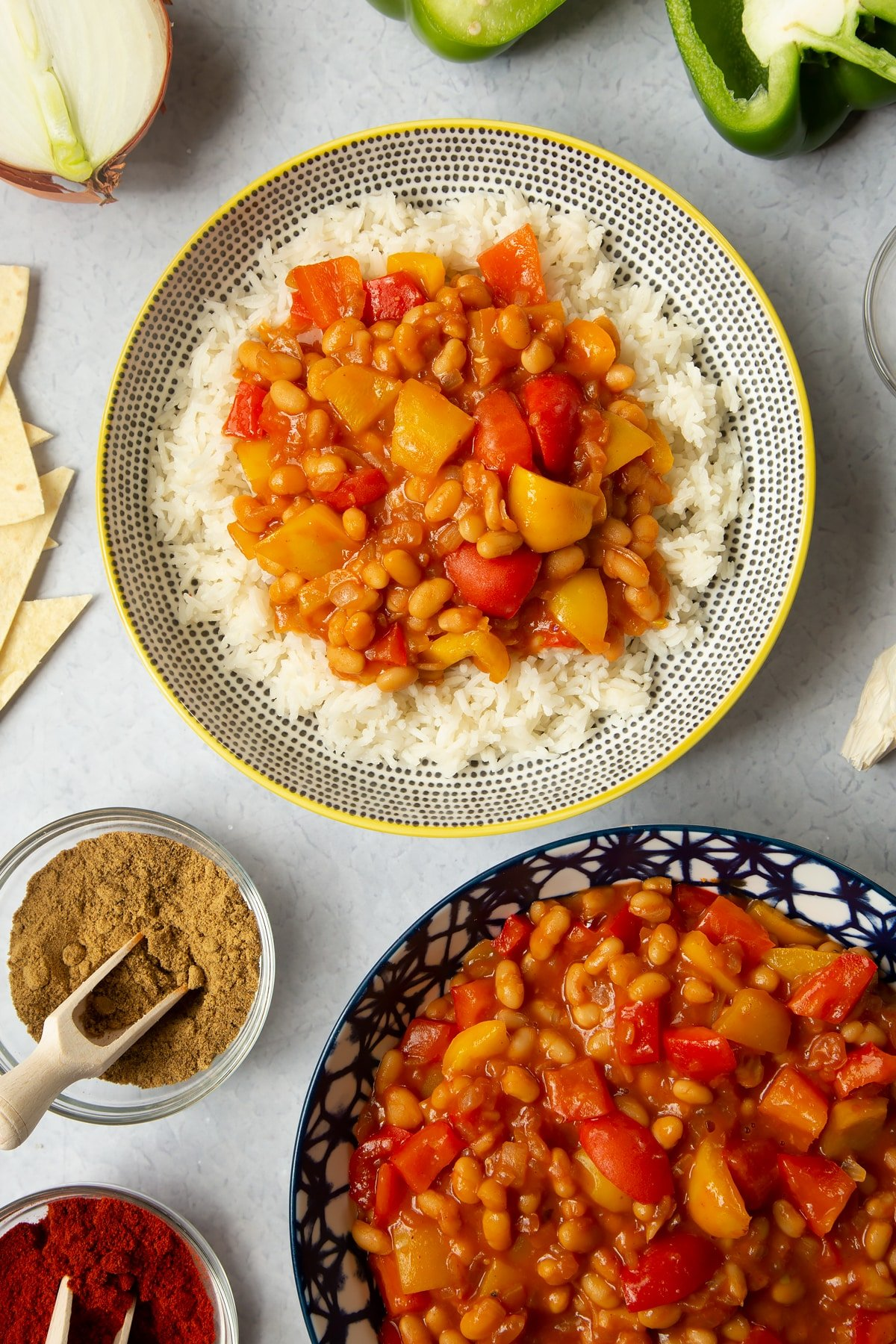 A 5 minute baked bean chilli served on a bed of rice in a bowl. More chilli is in a bowl to the side and ingredients to make the chilli surround the bowls.
