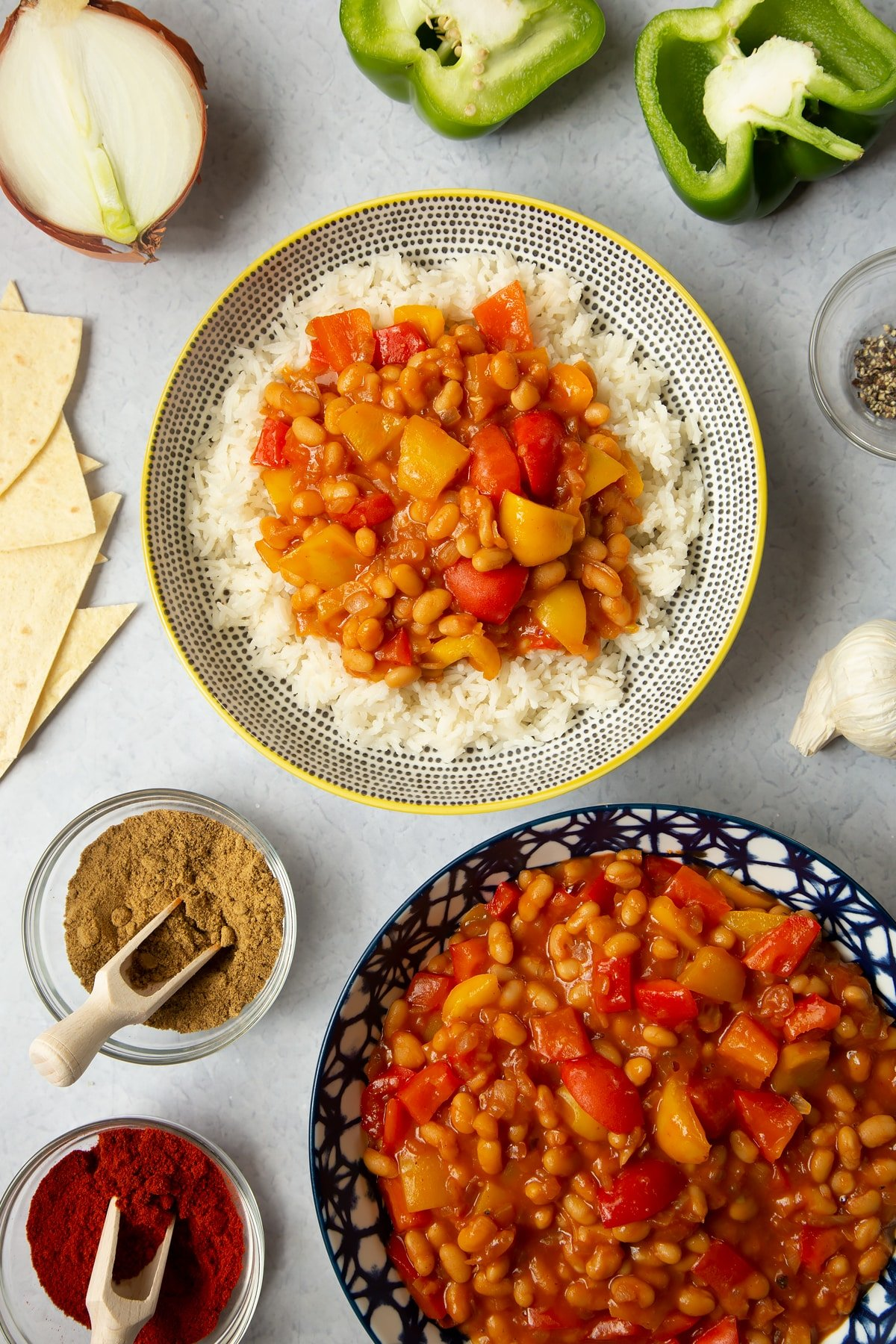 Baked bean chilli served on rice. Another bowl holds more chilli. Ingredients such as peppers, garlic and spices surround the bowls.