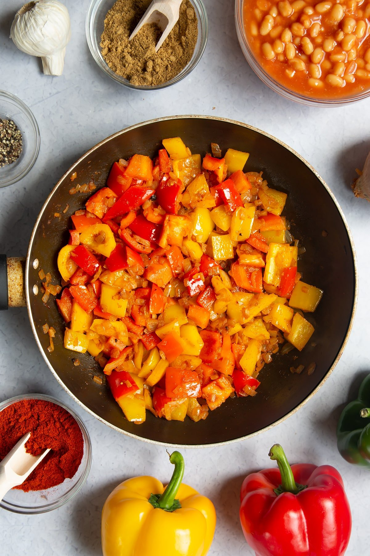 A frying pan containing fried onion, garlic, paprika, cumin, pepper and red and yellow peppers. Ingredients to make baked bean chilli surround the pan.