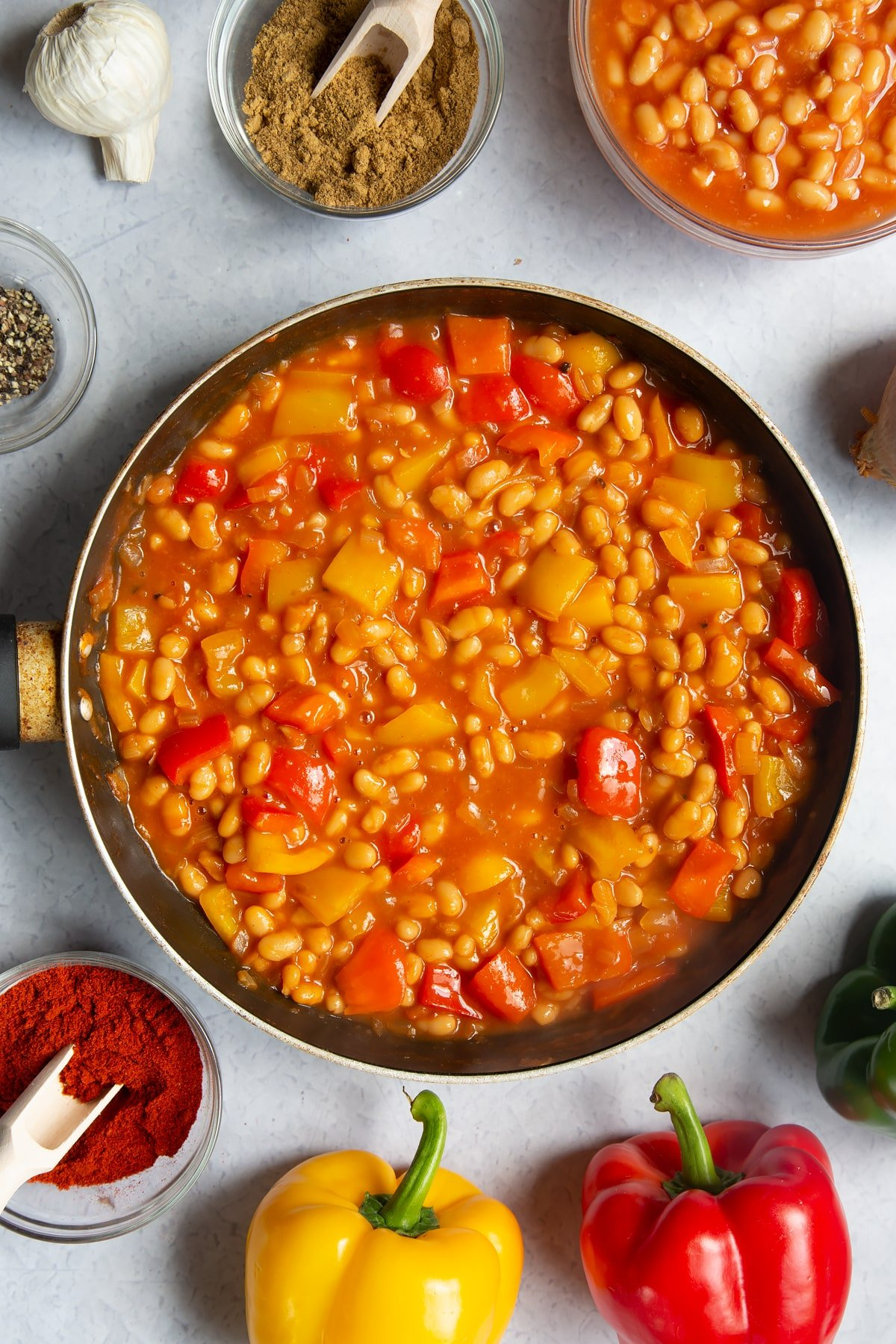 A frying pan containing fried onion, garlic, paprika, cumin, pepper and red and yellow peppers and baked beans. Ingredients to make baked bean chilli surround the pan.