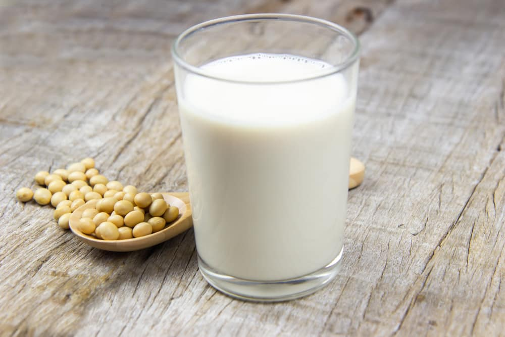 A glass of soy milk on a wooden table with a spoon of soy beans at the side.