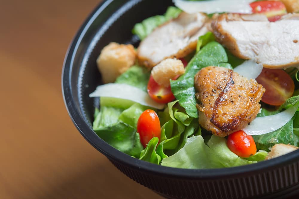 Plastic black bowl filled with chicken salad on a wooden table.