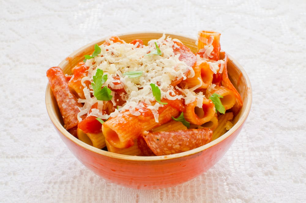 A bowl of pasta with pepperoni topped with grated cheese.