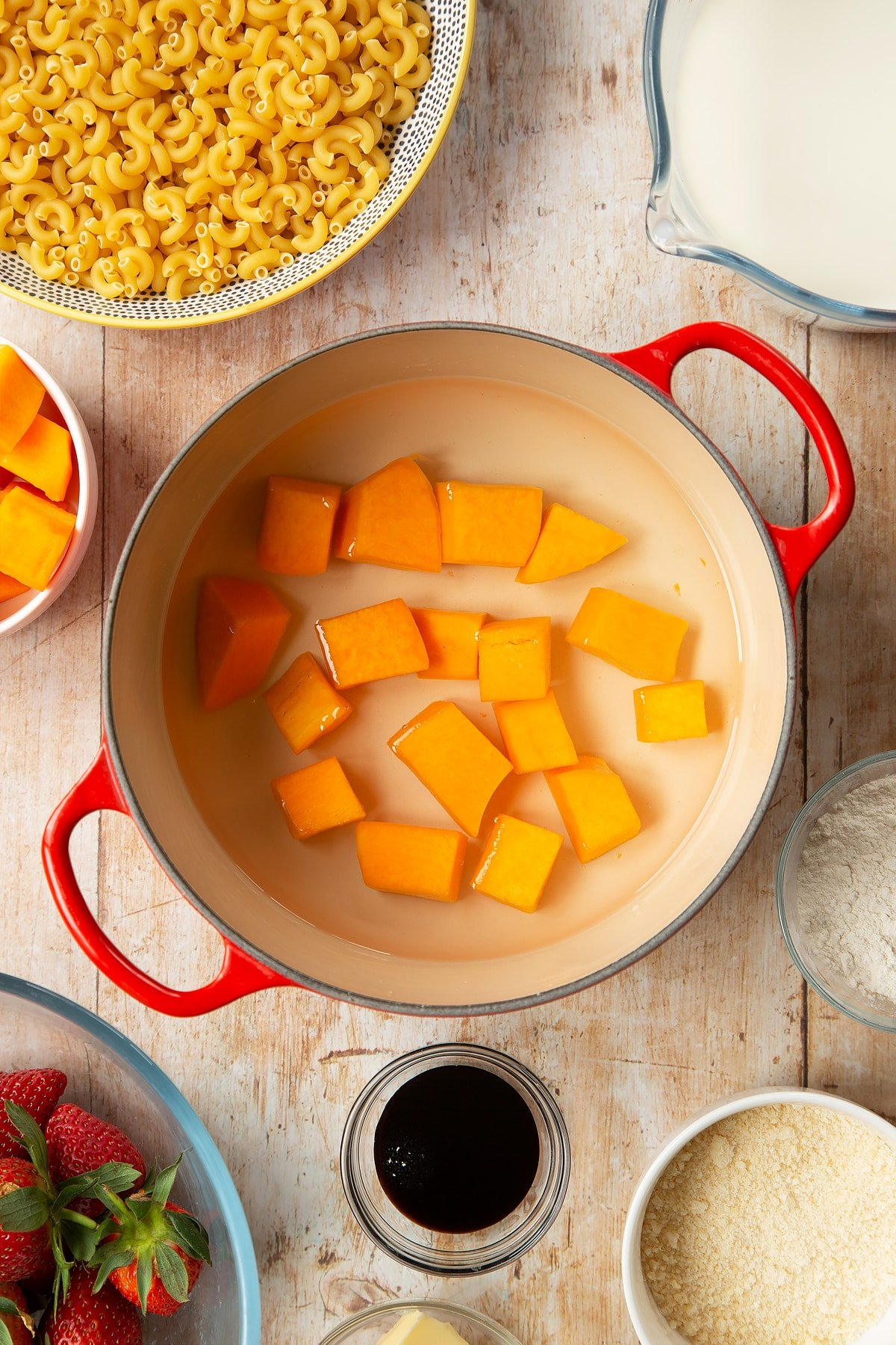 A saucepan containing chunks of butternut squash in water. The pan is surrounded by ingredients for strawberry pasta.