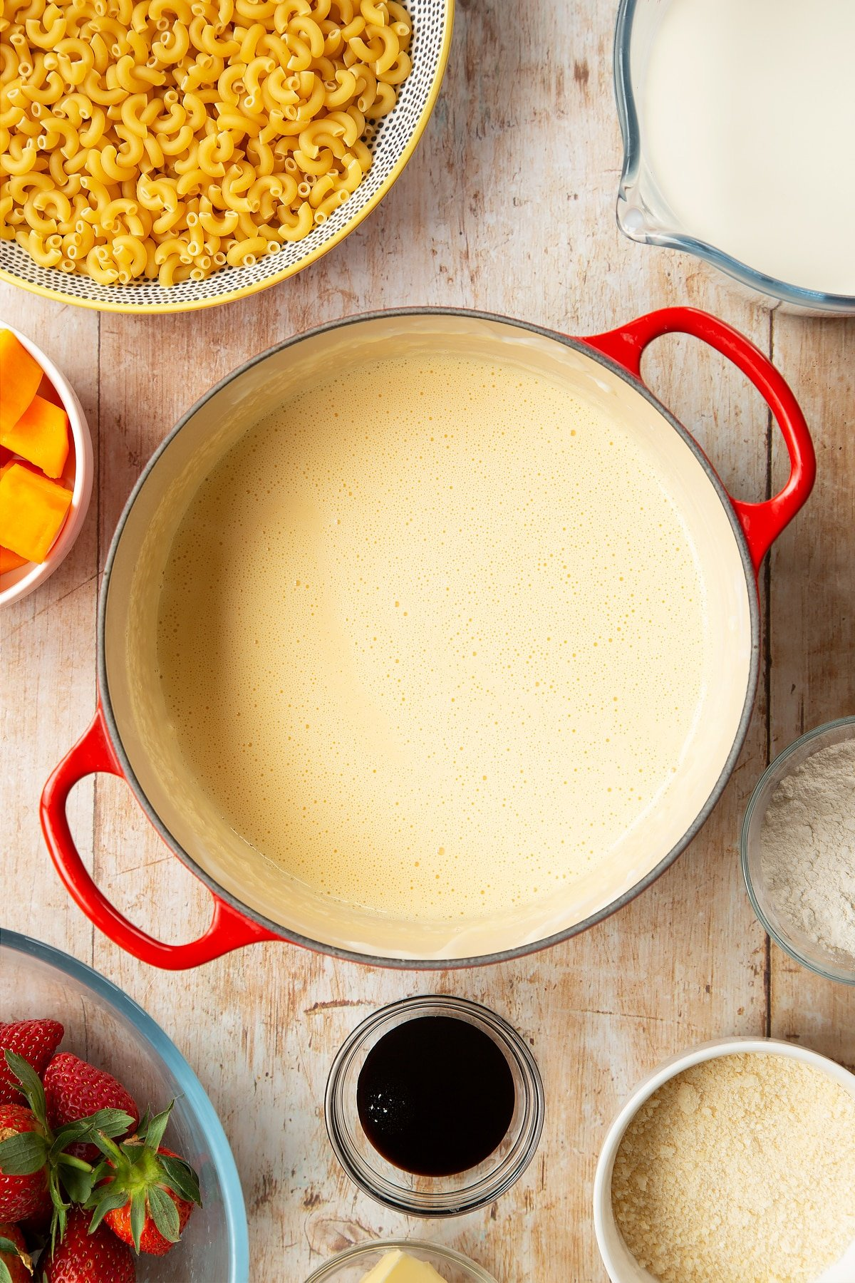 A saucepan containing a blended cheese sauce made with milk, butter, flour, Parmesan cheese and butternut squash. The pan is surrounded by ingredients for strawberry pasta.