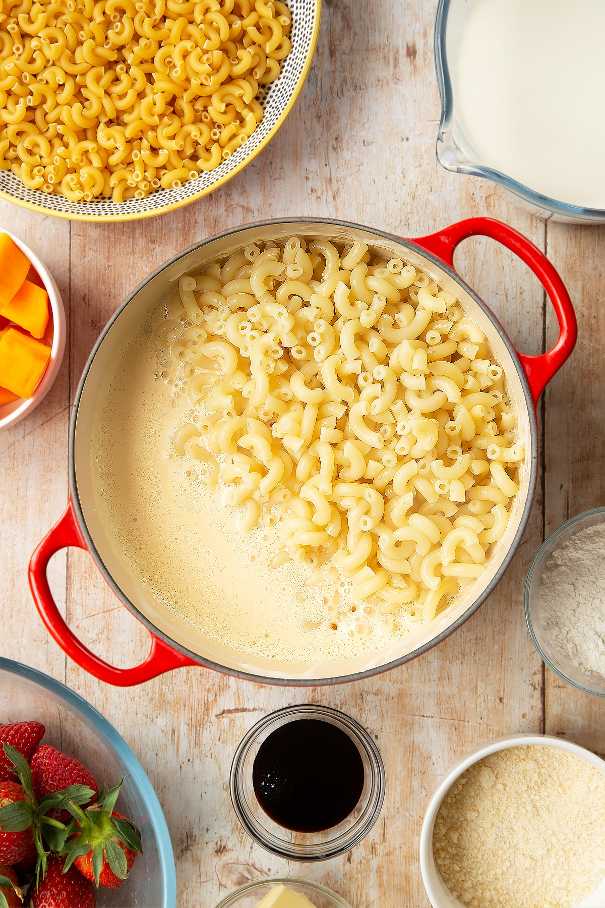 A saucepan containing a cheese and butternut squash sauce, topped with cooked macaroni. The pan is surrounded by ingredients for strawberry pasta.
