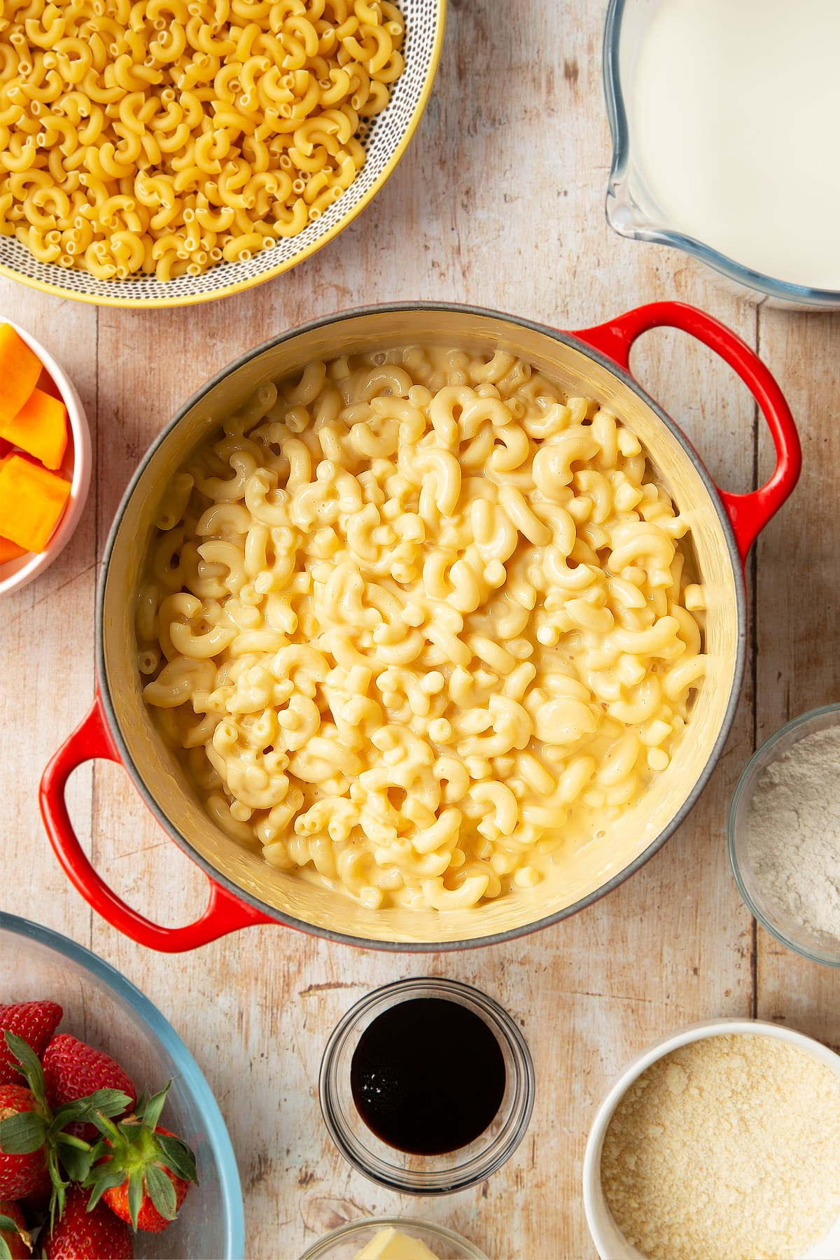 A saucepan containing macaroni stirred into a cheese and butternut squash sauce. The pan is surrounded by ingredients for strawberry pasta.