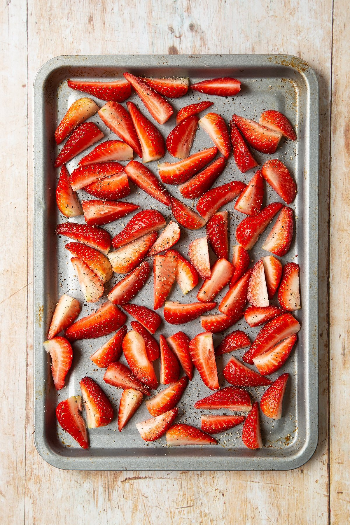 Strawberries sliced into quarters, seasoned with pepper on a non-stick tray.