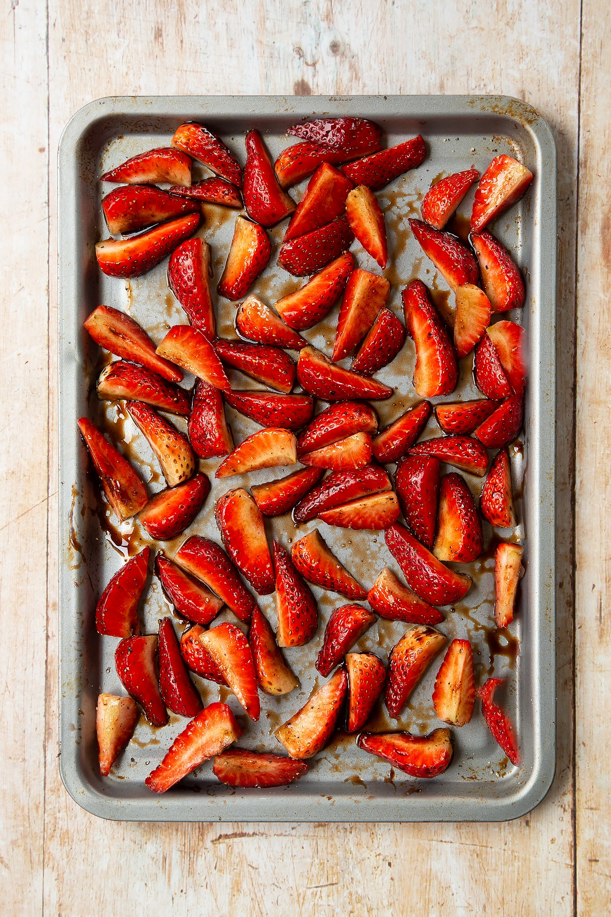Strawberries sliced into quarters and mixed with pepper and balsamic glaze. placed on a non-stick tray.