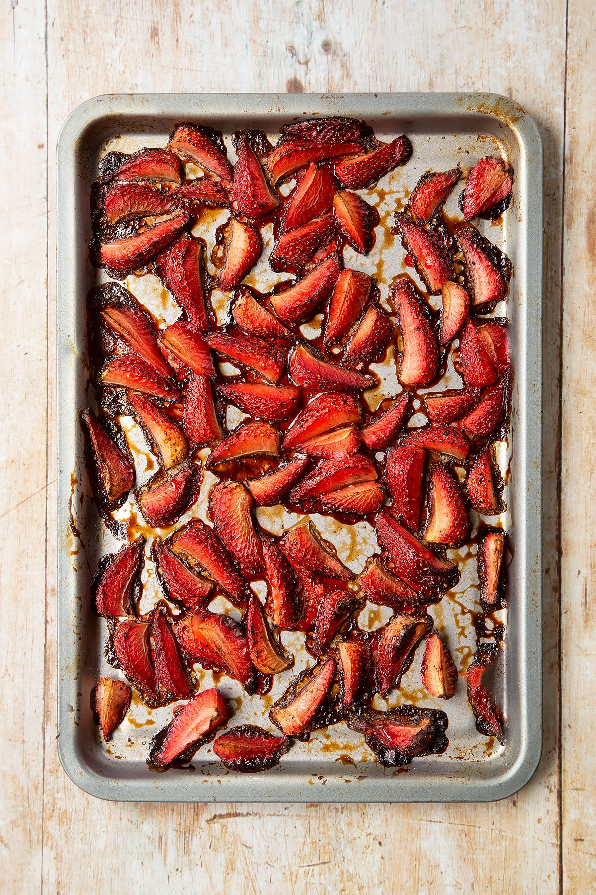 Roasted balsamic strawberries on a non-stick tray.