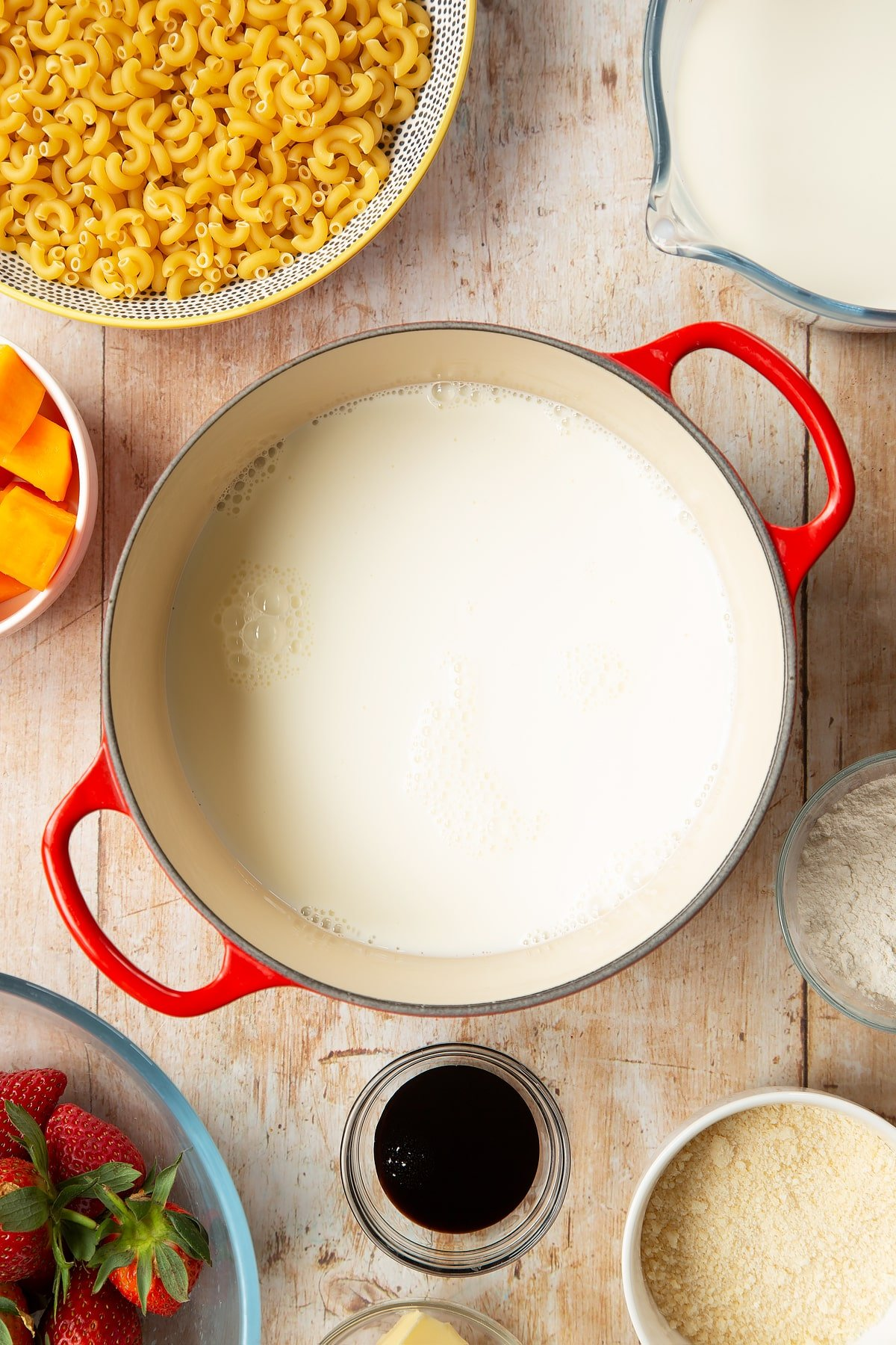 A saucepan containing milk. The pan is surrounded by ingredients for strawberry pasta.