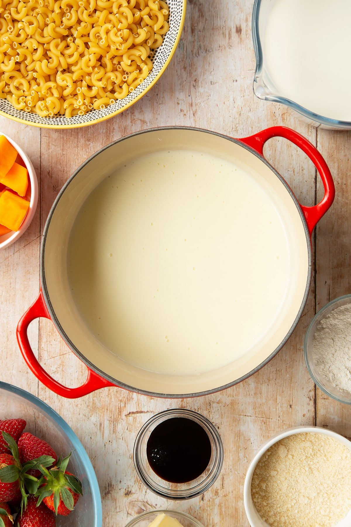 A saucepan containing a white sauce made with milk, butter and flour. The pan is surrounded by ingredients for strawberry pasta.