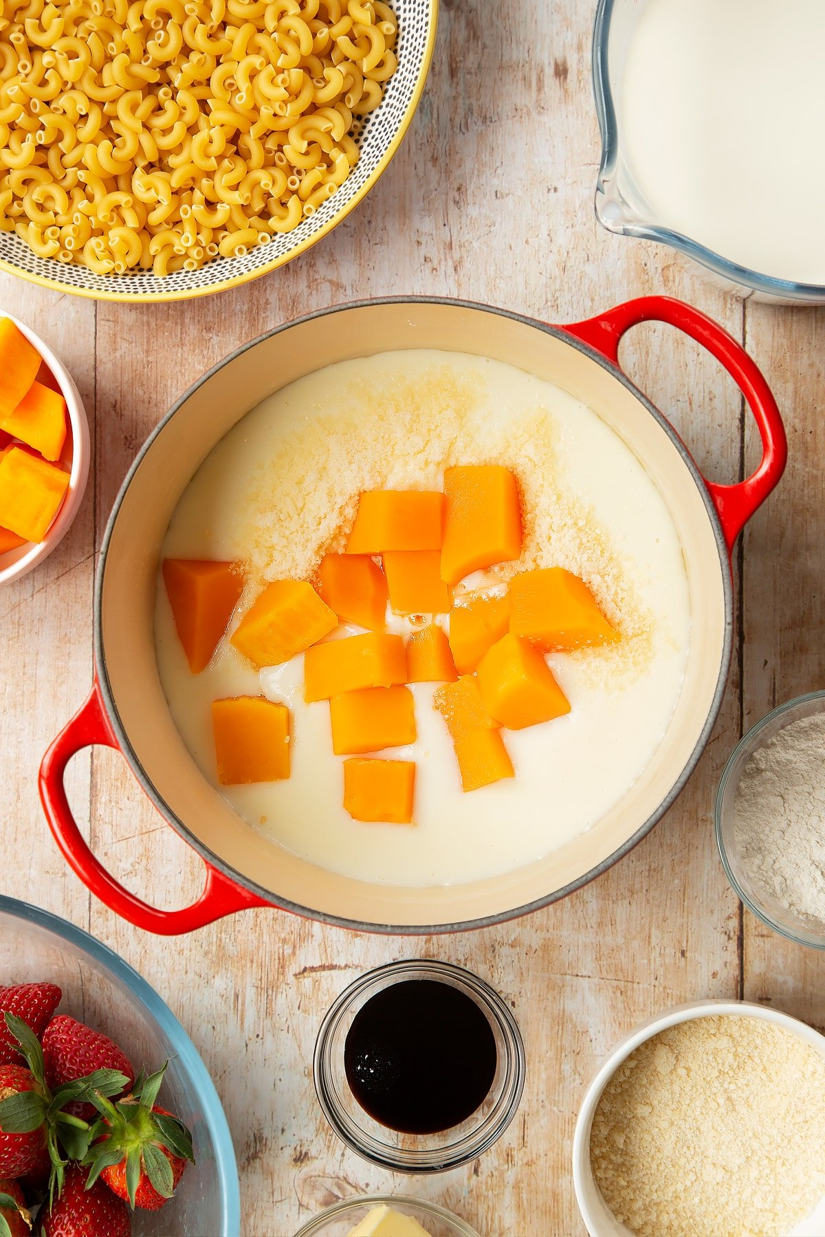 A saucepan containing a white sauce made with milk, butter and flour, topped with Parmesan cheese and butternut squash. The pan is surrounded by ingredients for strawberry pasta.