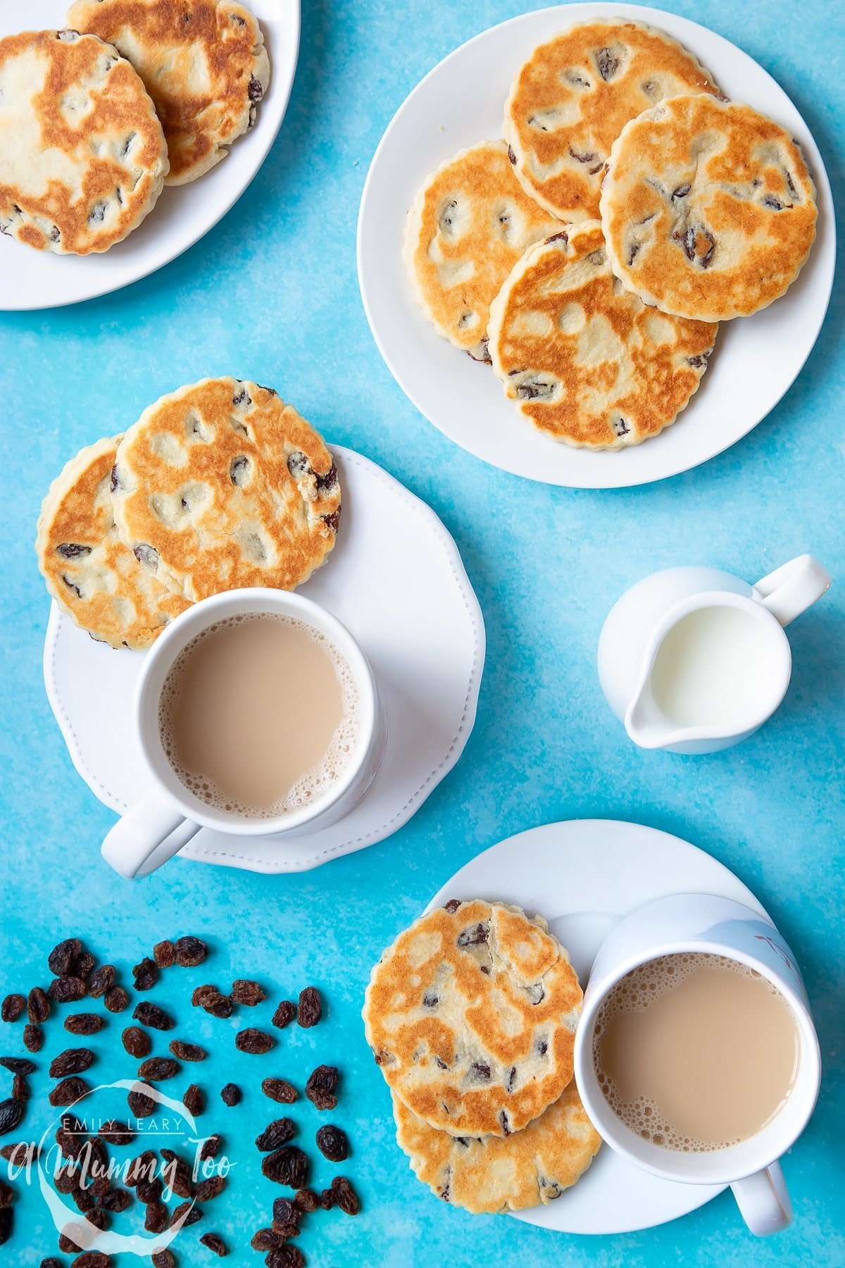 Welsh cakes on a number of white plates with cups of tea. A small jug of milk sits to one side by a scattering of sultanas.