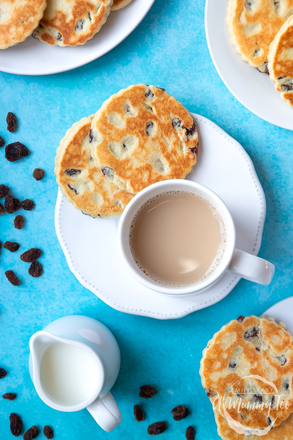 Welsh cakes on a white plate with a cup of tea. A small jug of milk sits to one side by a scattering of sultanas.