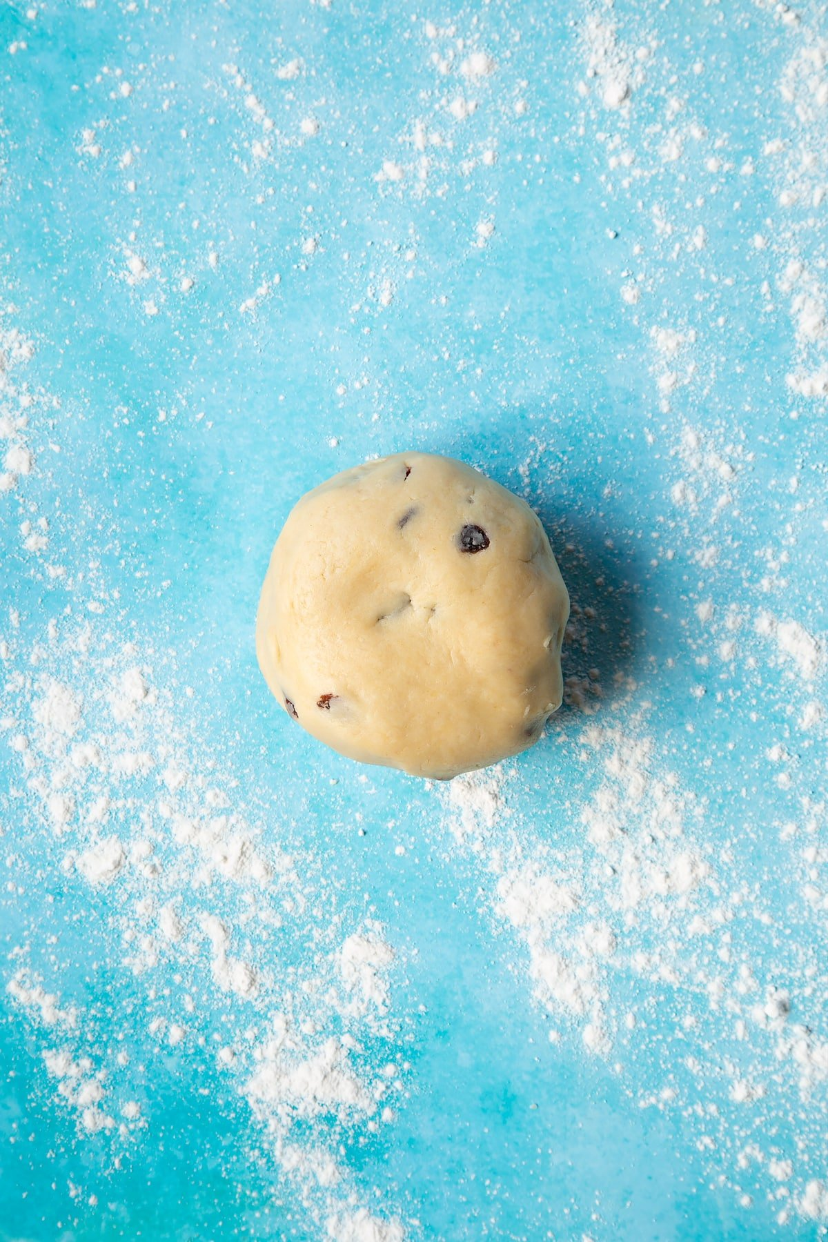 A Welsh cakes dough made from flour, butter, egg, sugar and sultanas on a floured surface.