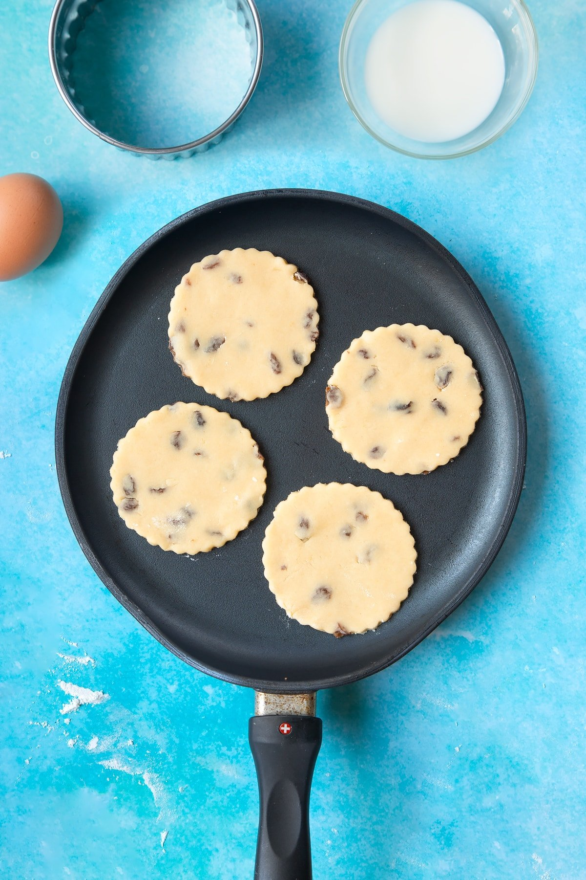 Welsh cake dough rounds cooking in a hot, flat pan.