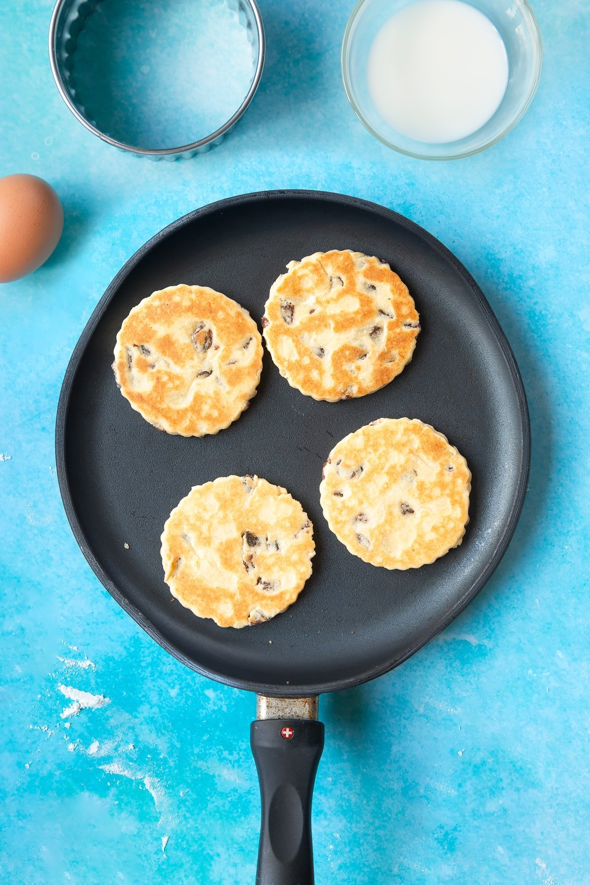 Cooked Welsh cake dough rounds in a hot, flat pan.