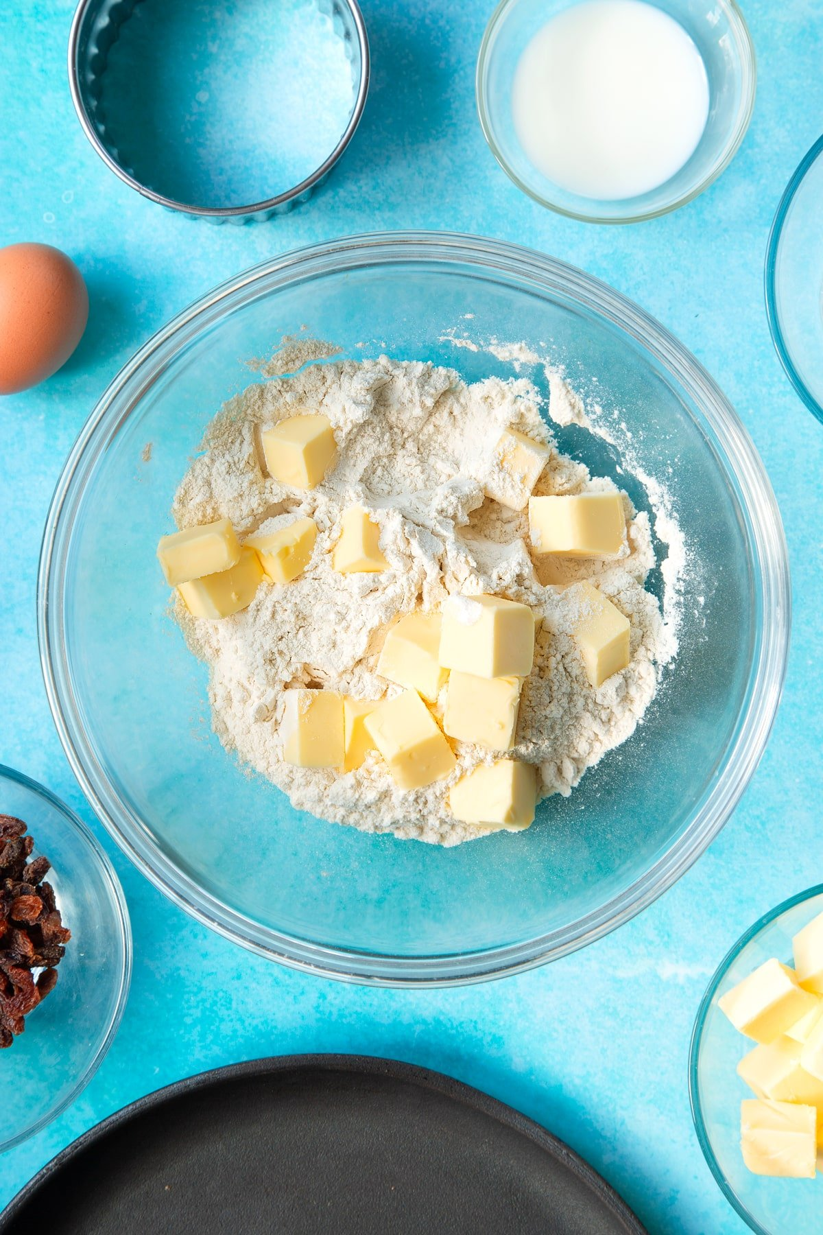Flour and cubed butter in a bowl. Ingredients and equipment to make Welsh cakes surround the bowl.