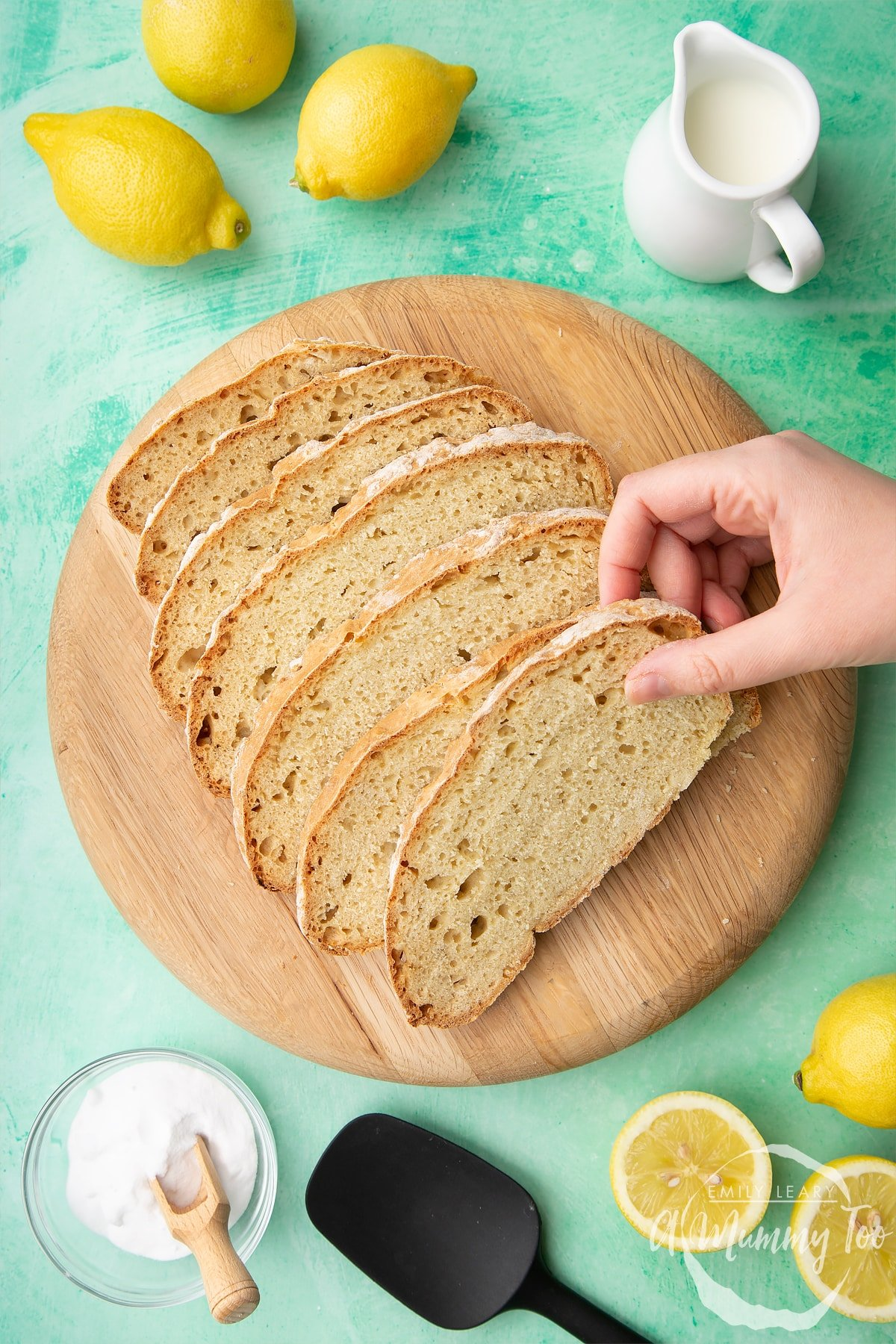Sliced soda bread without buttermilk on a wooden board.  A hand reaches in to take a slice. Lemon, milk and bicarbonate of soda are placed around the board.