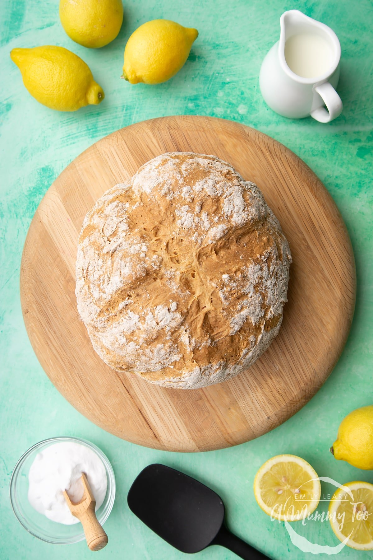 Soda bread without buttermilk on a wooden board. Lemon, milk and bicarbonate of soda are placed around the board.