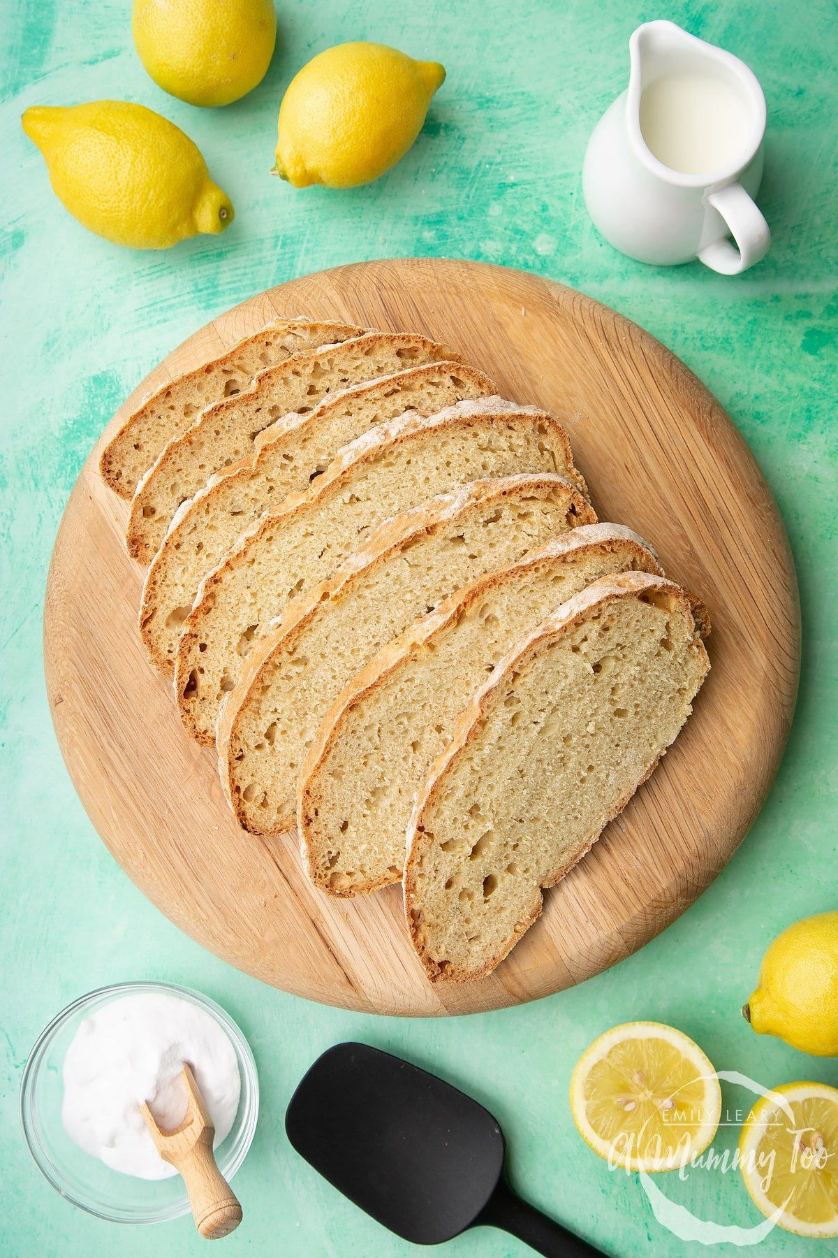 Sliced soda bread without buttermilk on a wooden board. Lemon, milk and bicarbonate of soda are placed around the board.