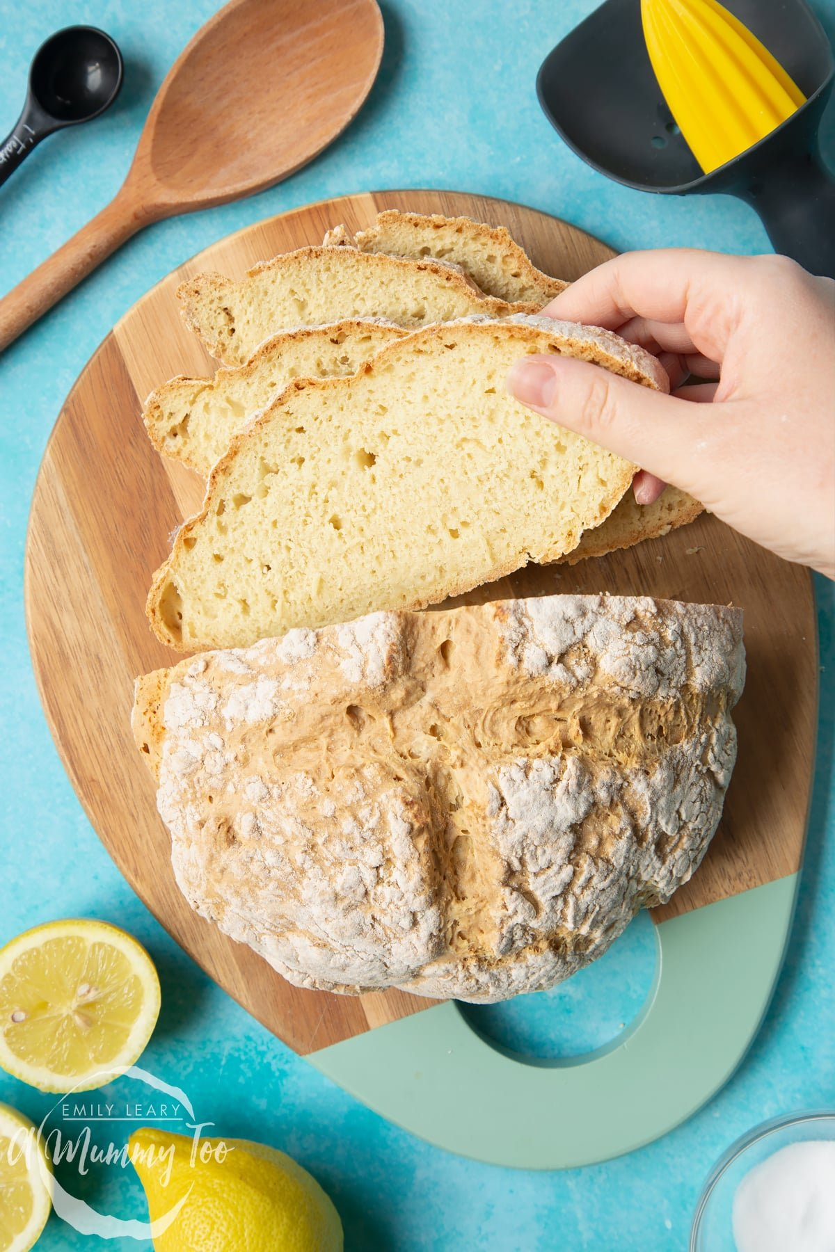 Vegan soda bread on a wooden board. Some of the bread has been cut into slices. A hand is taking a slice.