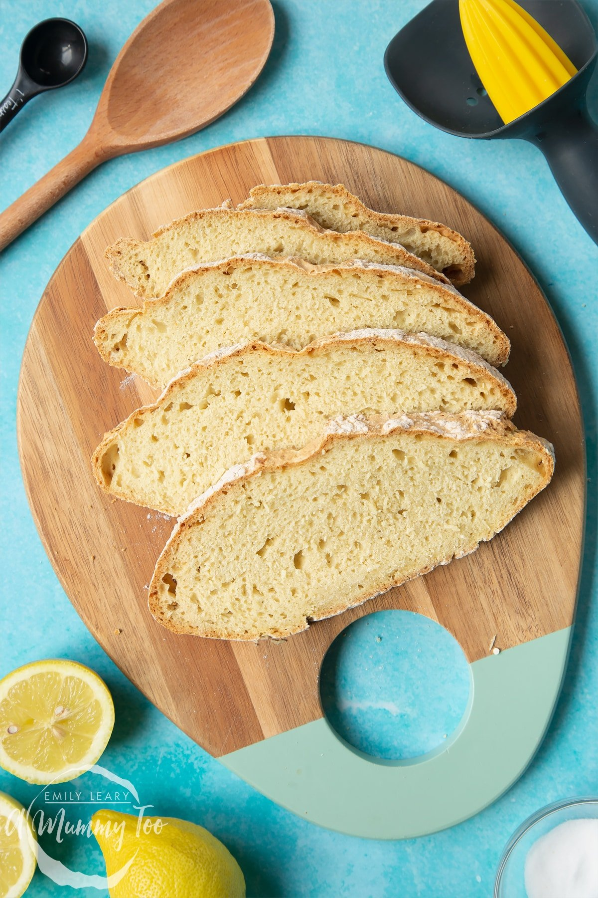 Vegan soda bread slices on a wooden board. Lemons and utensils surround the board.