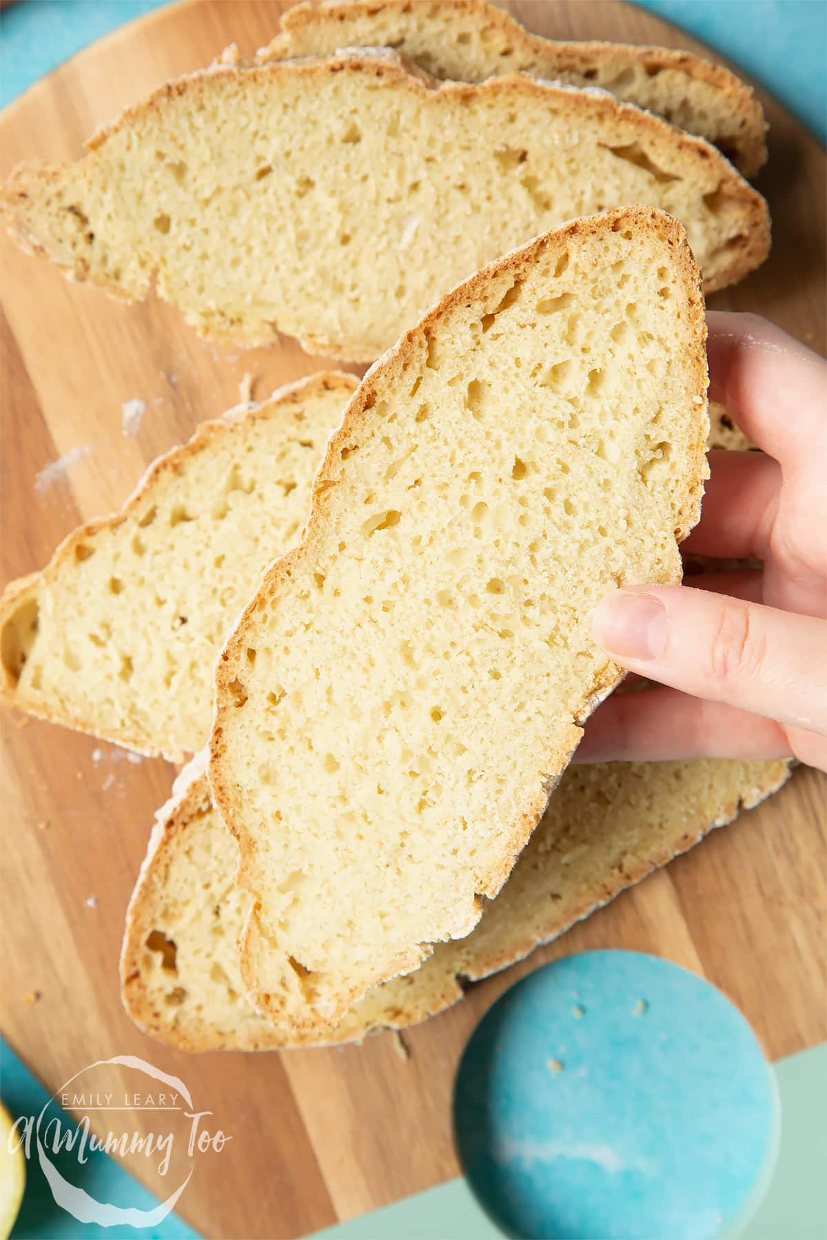 Vegan soda bread slices on a wooden board. A hand holds a slice.