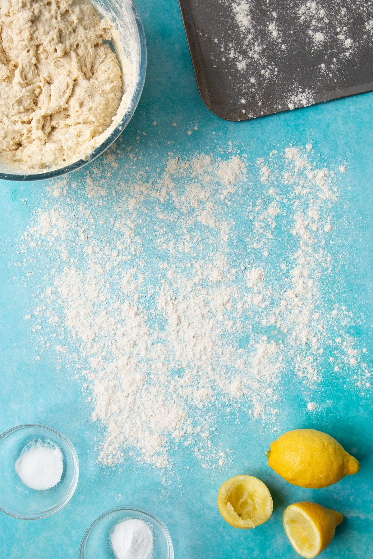 A floured surface surrounded by ingredients to make vegan soda bread.
